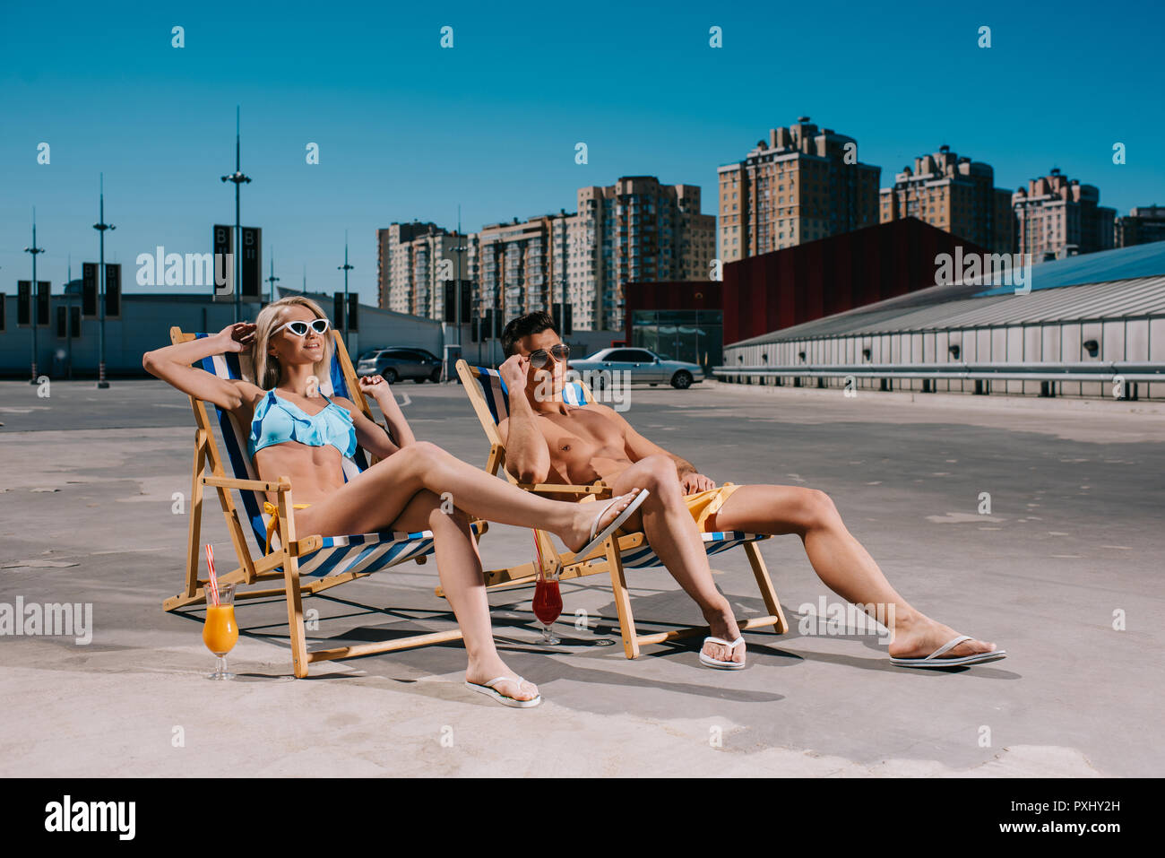 young attractive couple relaxing on sun loungers relaxing on parking - Stock Image