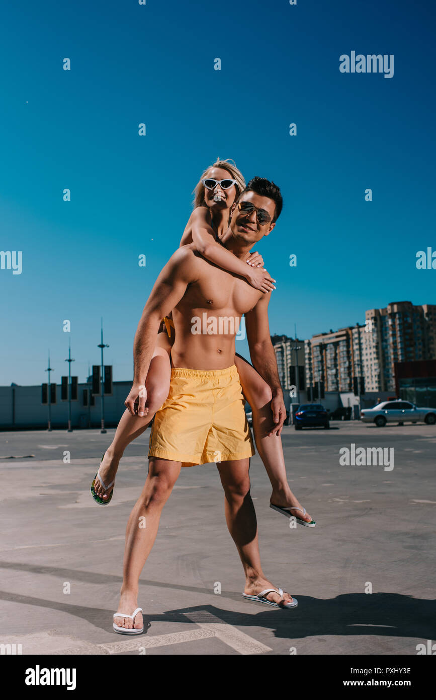 young attractive woman piggybacking on boyfriend on parking - Stock Image