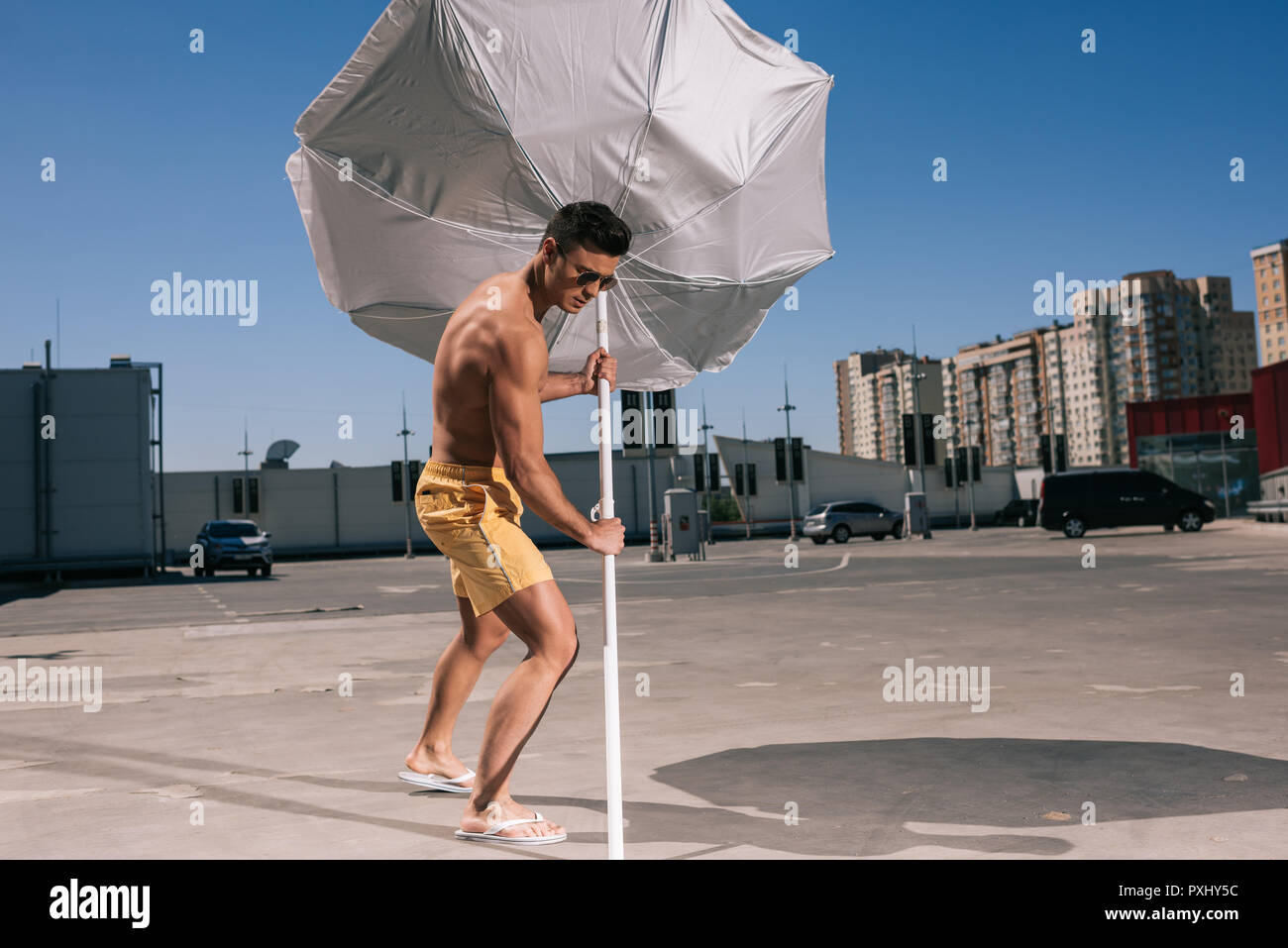 masculine young shirtless man putting beach umbrella in asphalt on parking - Stock Image