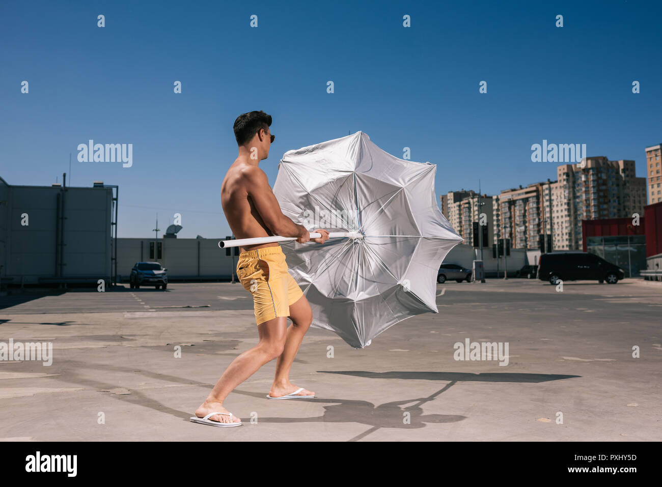 handsome young shirtless man with beach umbrella on parking - Stock Image