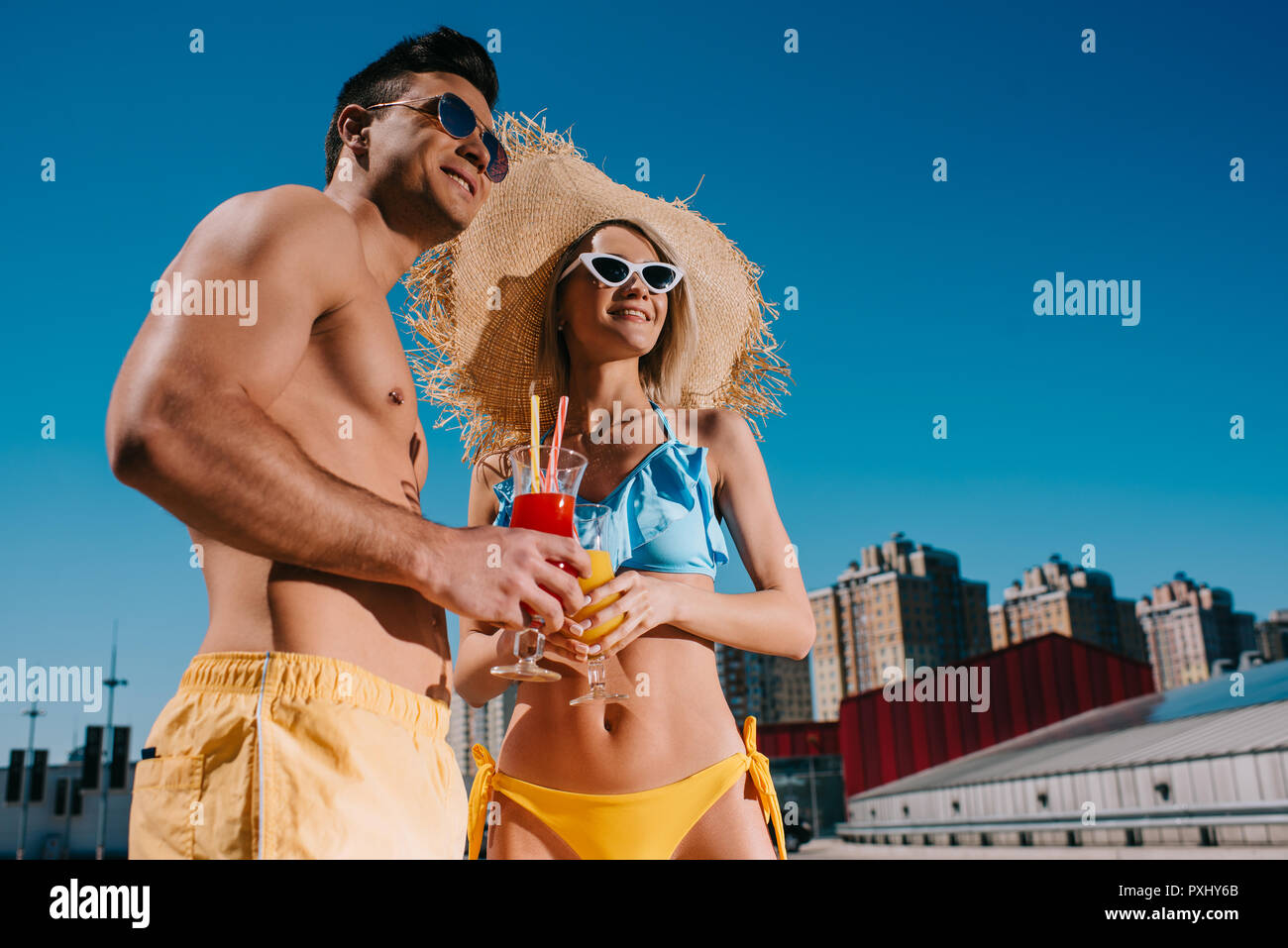 bottom view of young couple in swimsuits with refreshing cocktails in city - Stock Image