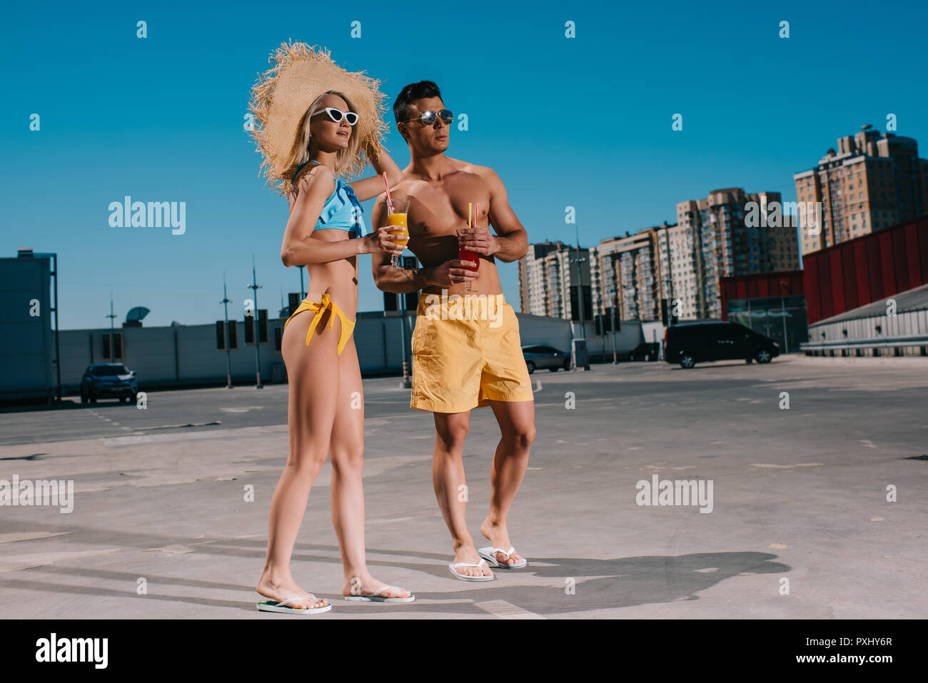 happy young couple in beach clothes with refreshing cocktails standing on parking - Stock Image
