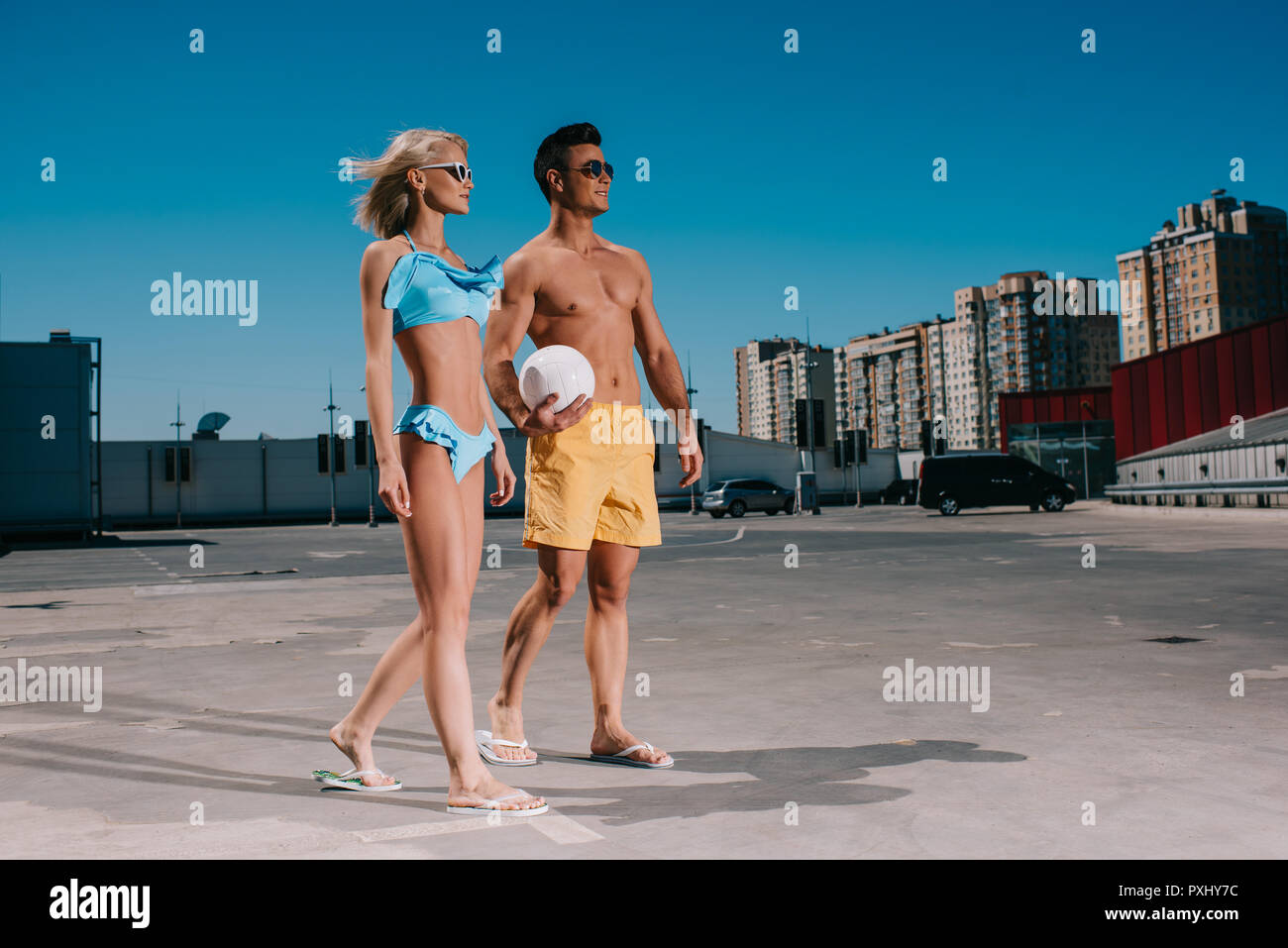 young couple in beach clothes with volleyball ball on parking - Stock Image