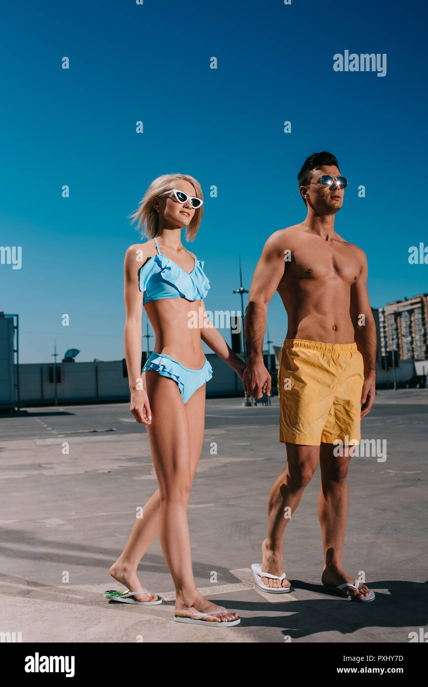 young couple in beach clothes holding hands and walking on parking - Stock Image