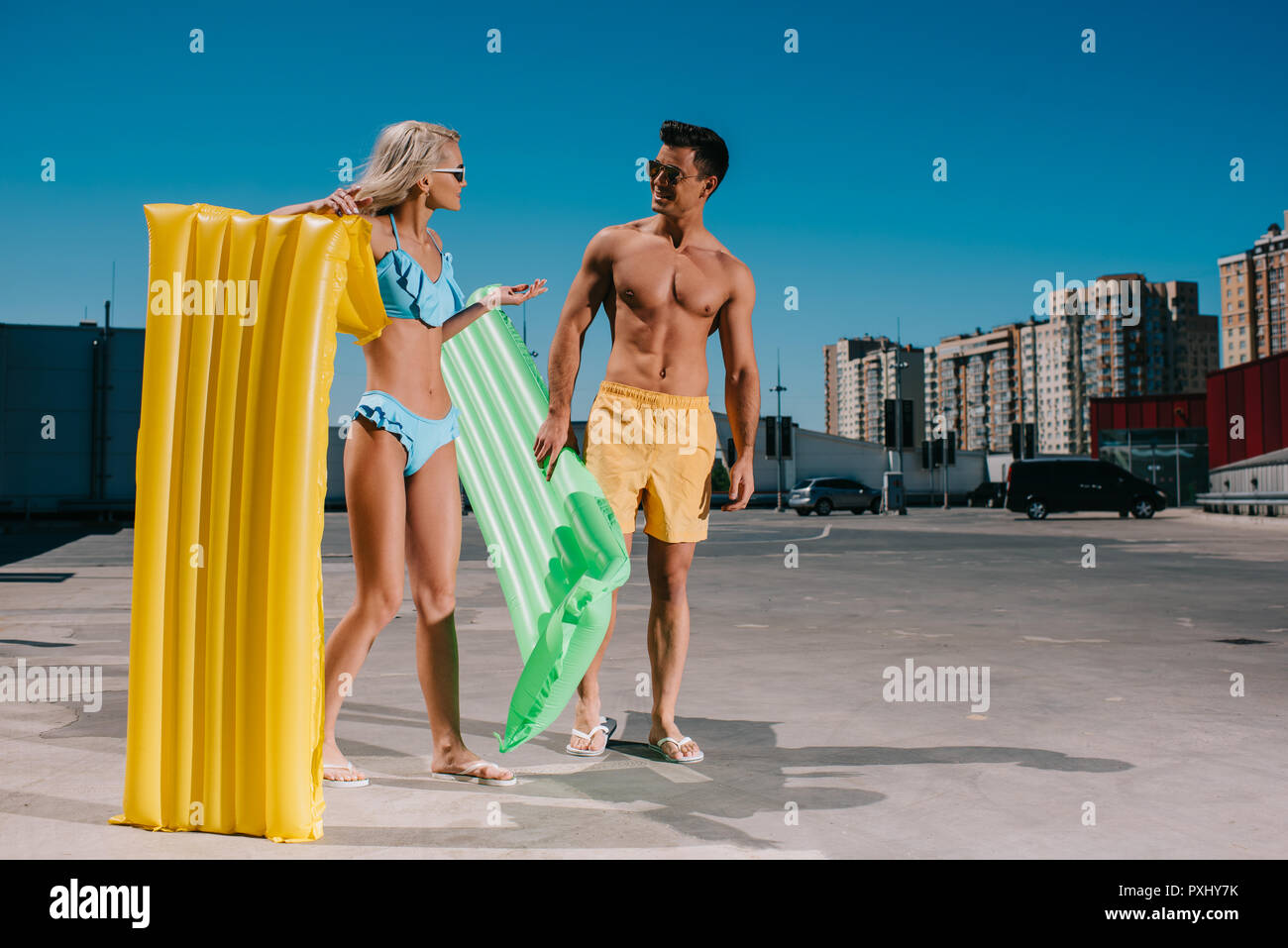 attractive young couple in beach clothes with inflatable beds on parking - Stock Image