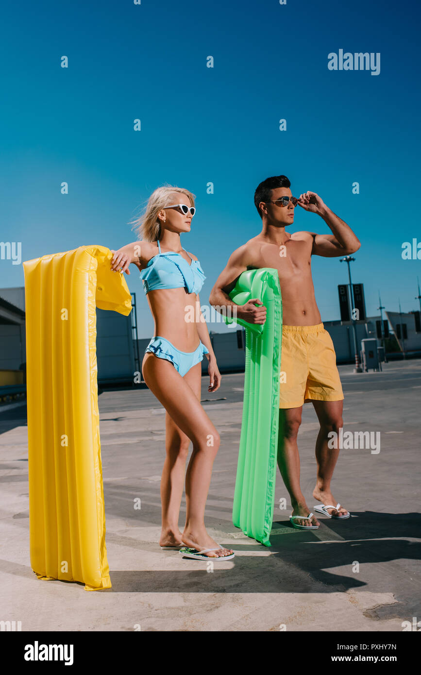 young couple in beach clothes with inflatable beds standing on parking - Stock Image