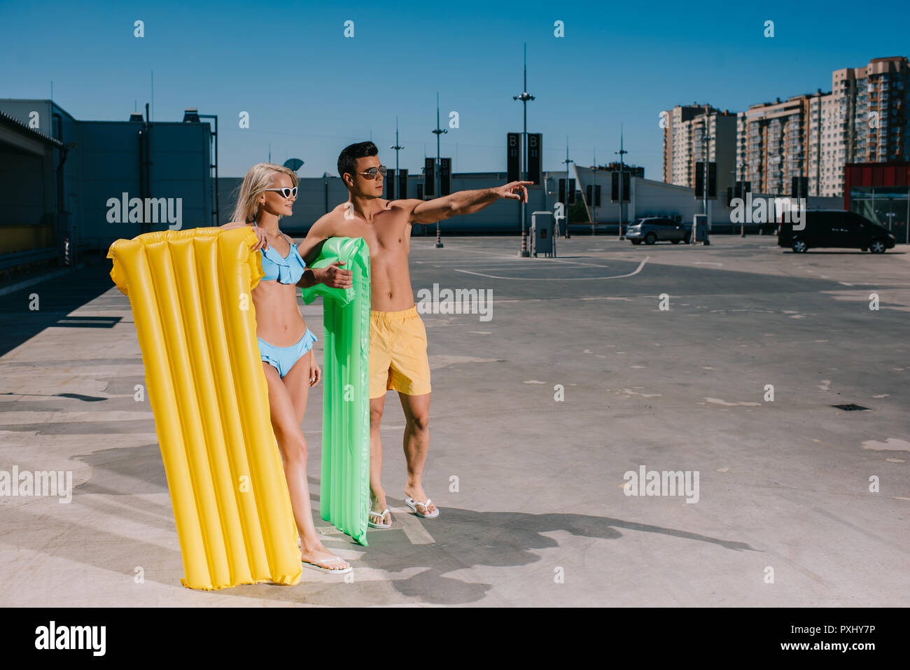 happy young couple in beach clothes with inflatable beds on parking - Stock Image