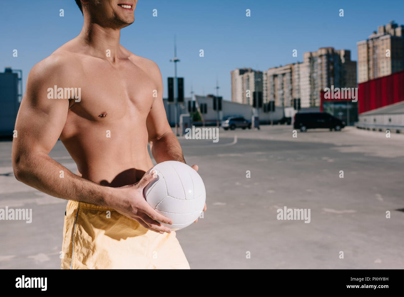cropped shot of young shirtless man holding volleyball ball on parking - Stock Image