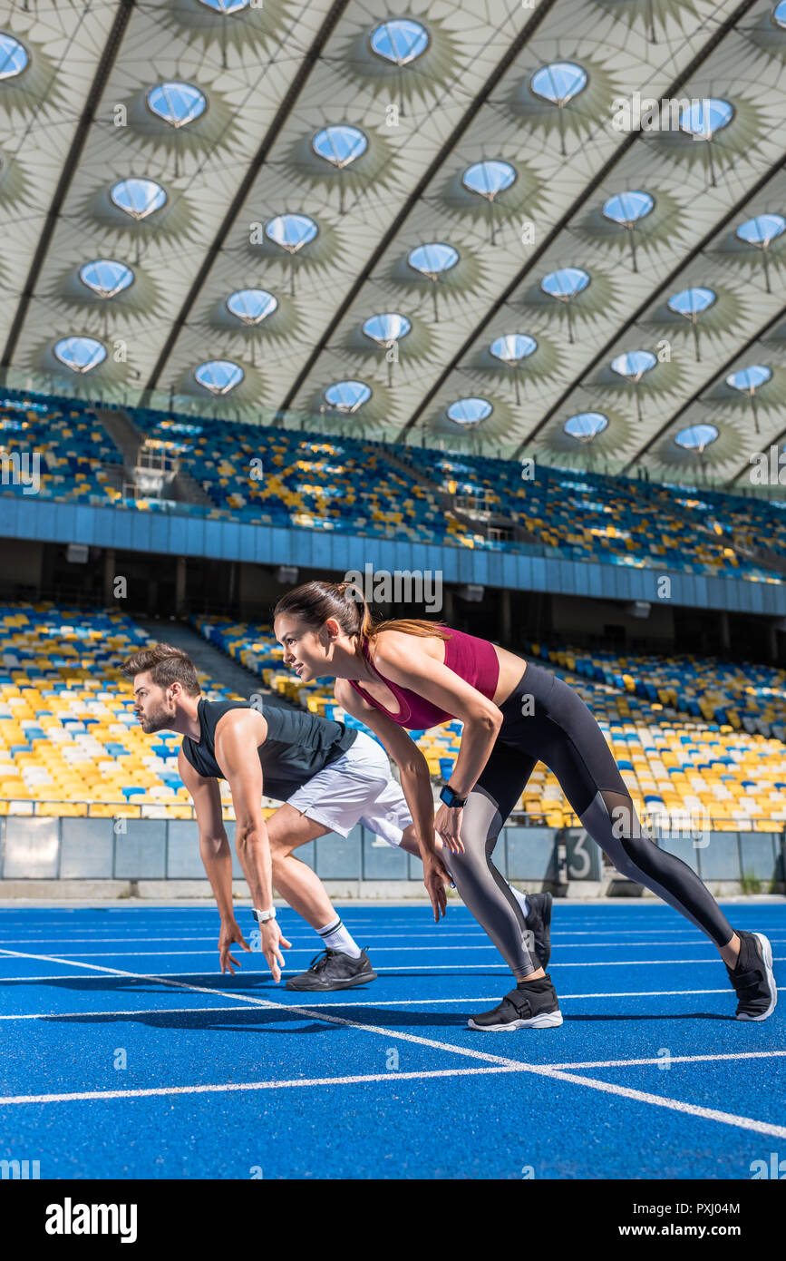 fit young male and female sprinters in start position on running track at sports stadium - Stock Image