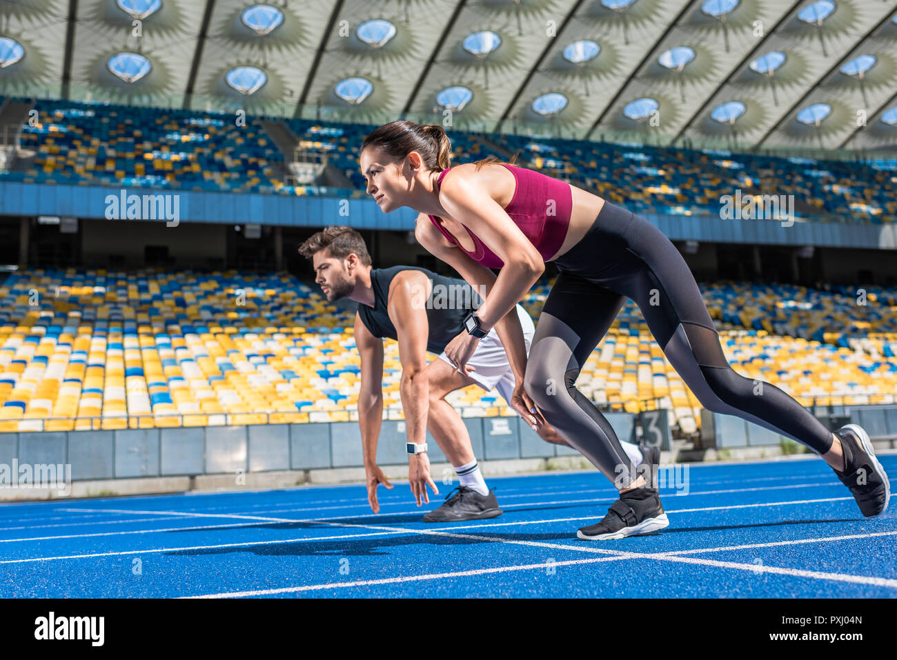 athletic young male and female sprinters in start position on running track at sports stadium - Stock Image