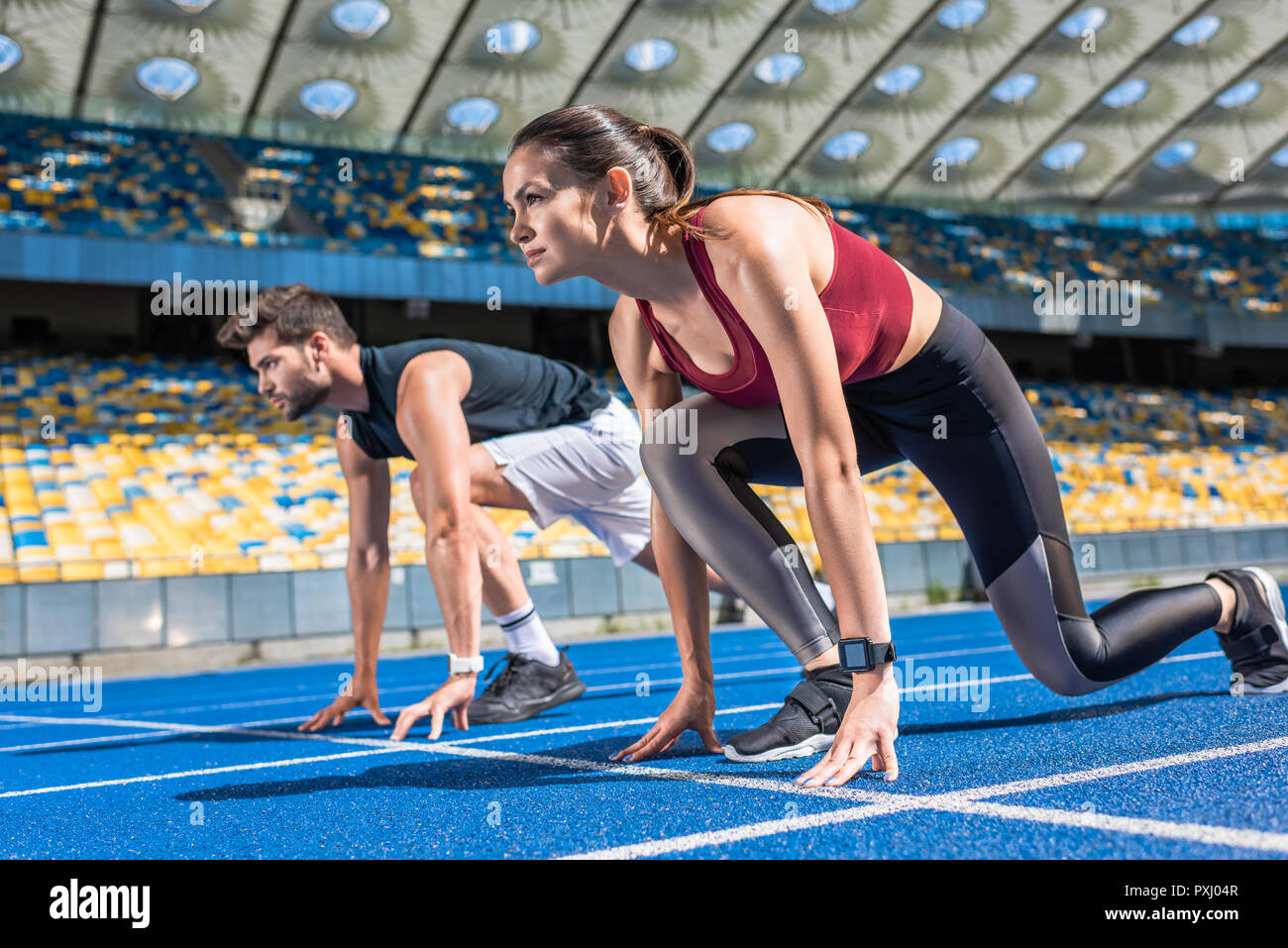 sportive young male and female sprinters in start position on running track at sports stadium - Stock Image