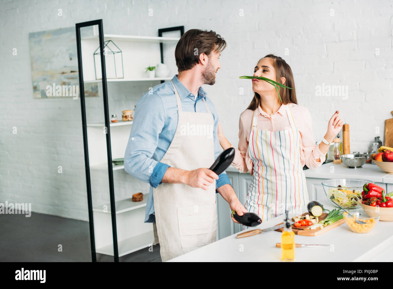 couple grimacing with vegetables while cooking in kitchen Stock Photo