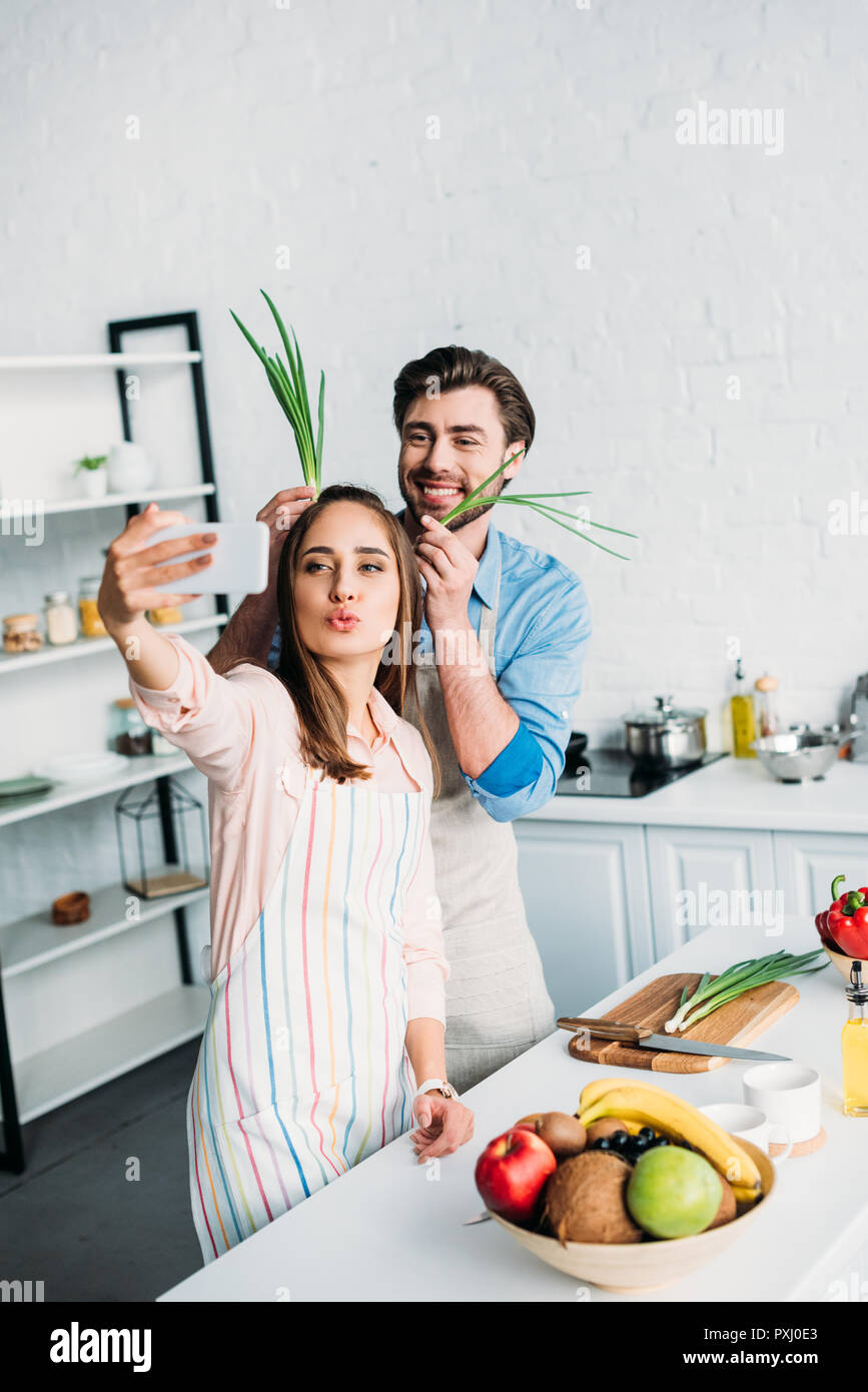 couple taking selfie while having fun during cooking in kitchen - Stock Image