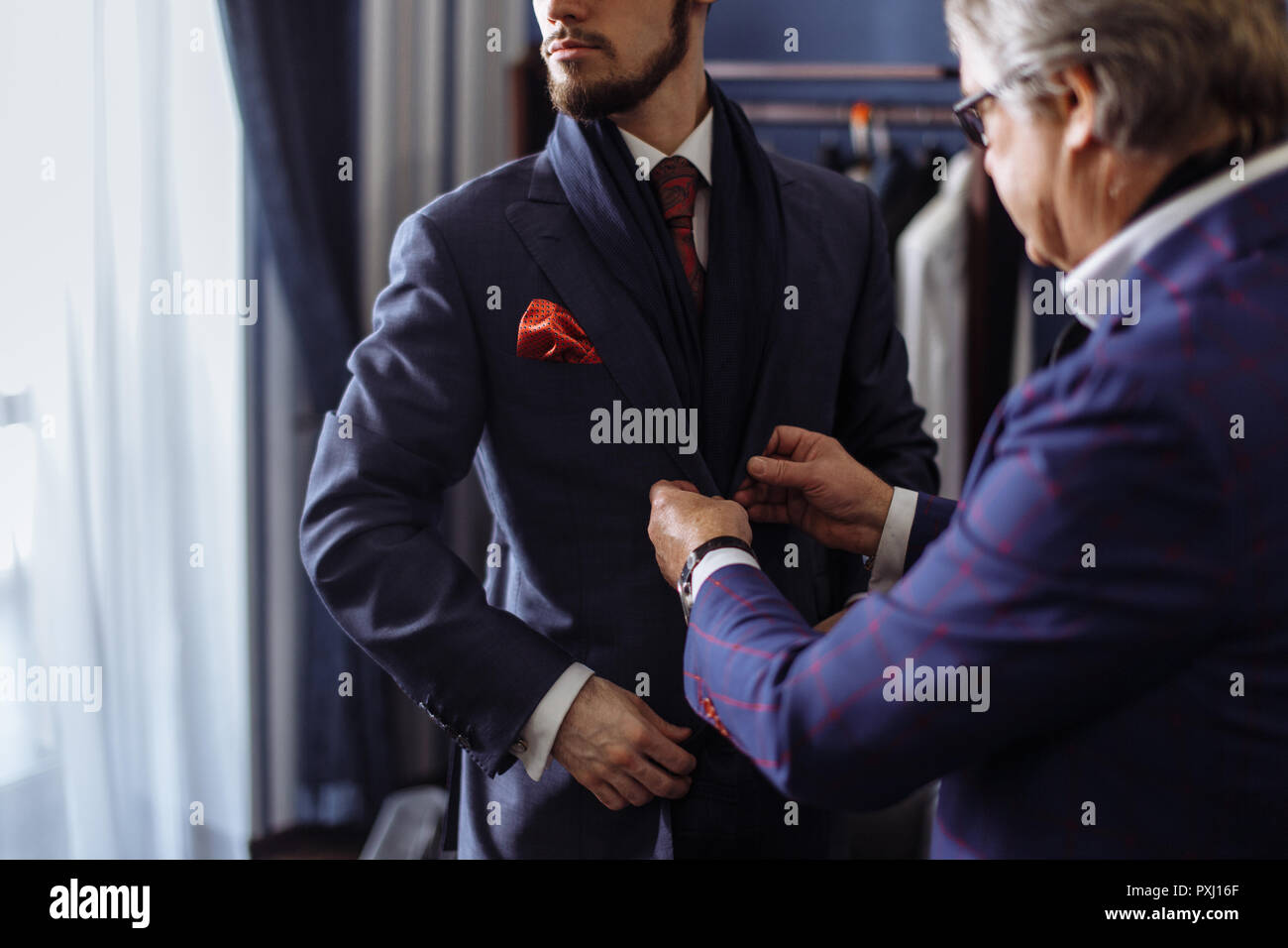 Tailor with client in atelier. Sewing custom made suit - Stock Image