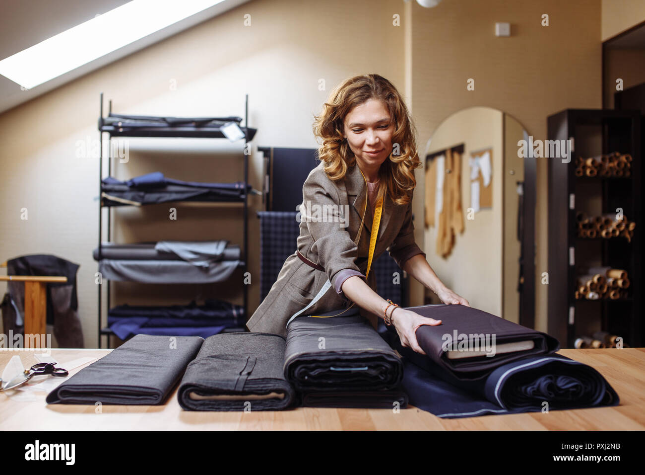 Female tailor choosing fabric for pattern cutting. Men's Wear industry, tailoring process Concept - Stock Image