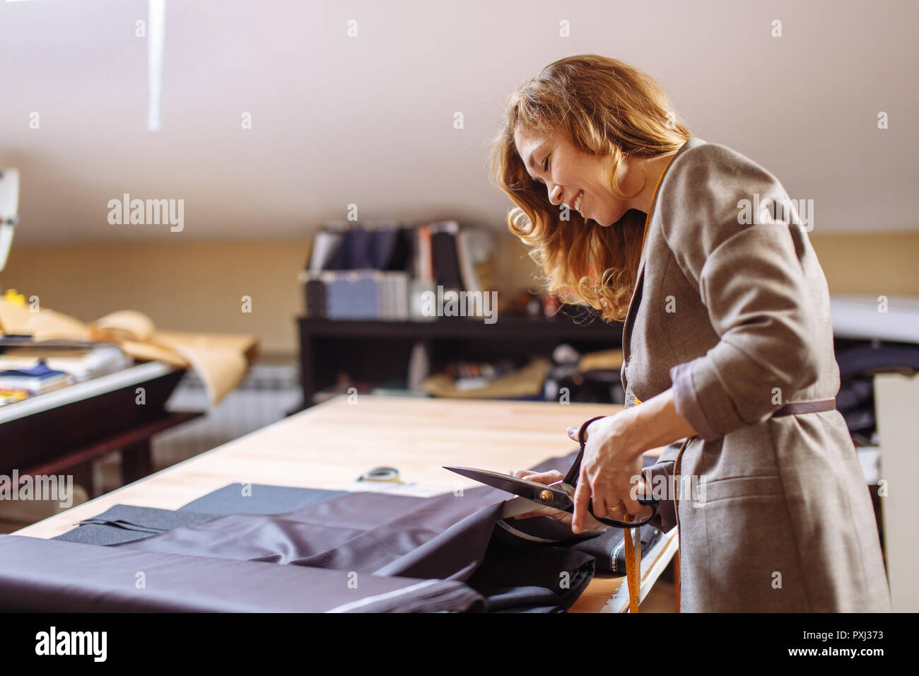 Female fashion designer working on suiting fabric with dressmaking accessories on table - Stock Image