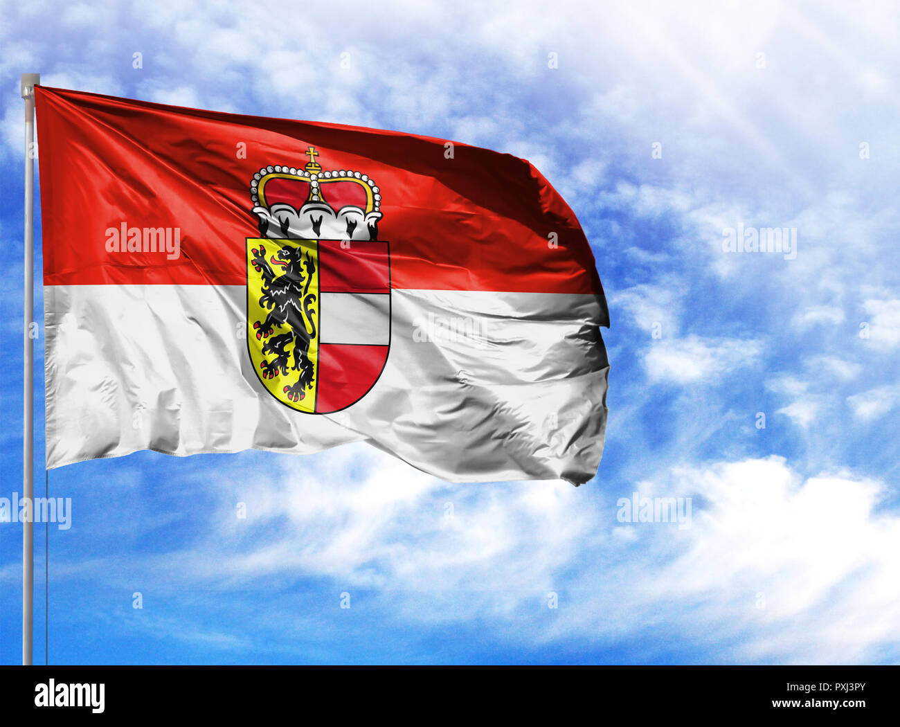 National flag of Salzburg on a flagpole in front of blue sky. - Stock Image