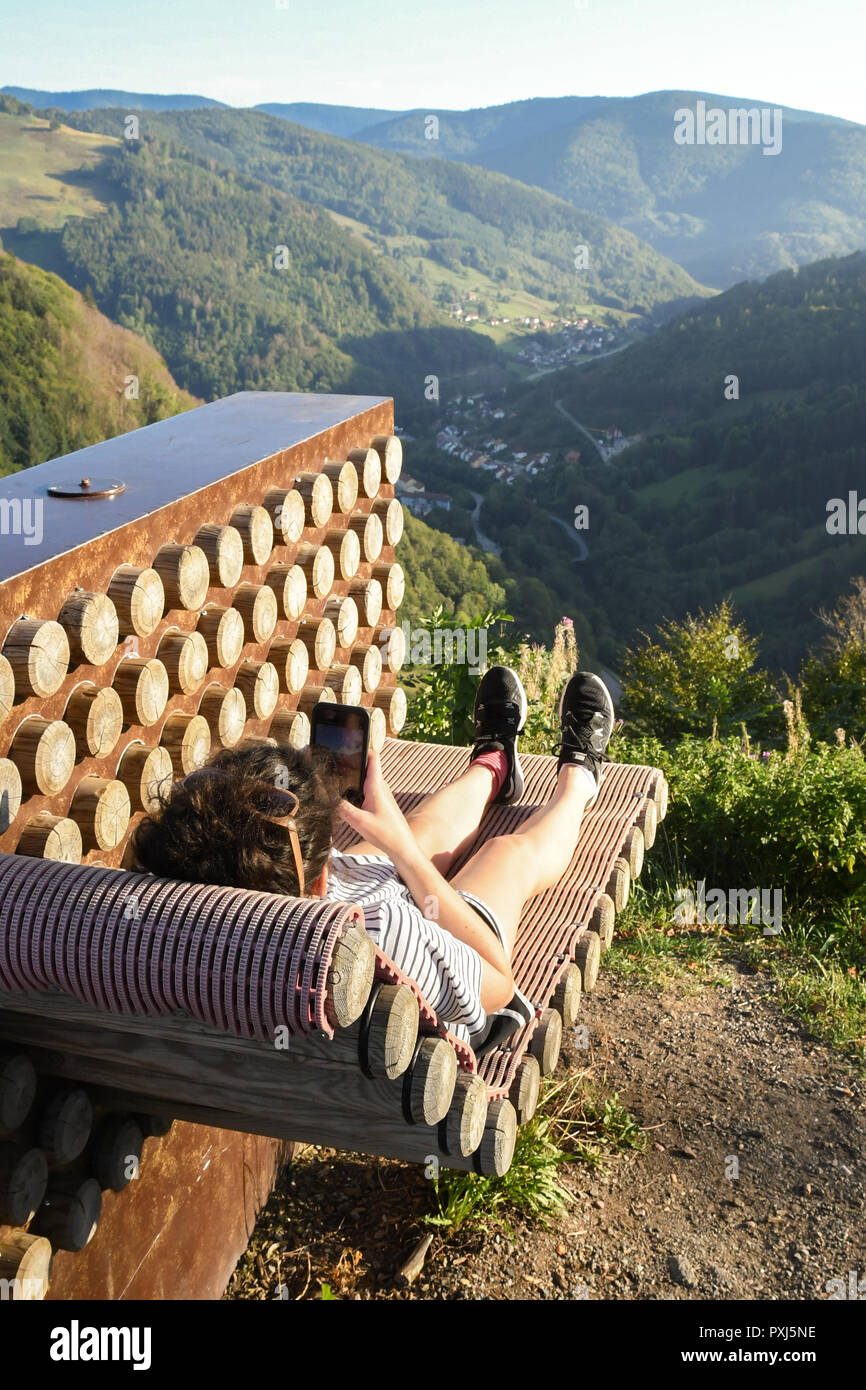 instagram moment - young woman taking photograph of feet on sun lounger and view of the Black Forest near Todtnauer Waterfall, Germany - Stock Image