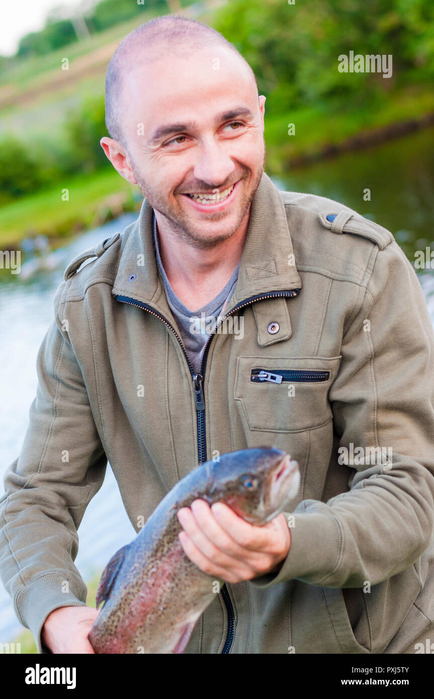 Young, unshaved, happy, fishing man smiling and holding caught Trout fish in his hands. - Stock Image