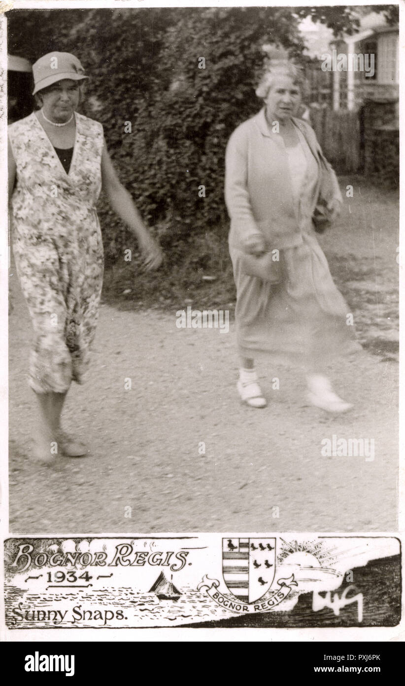 Sunny Snaps postcard - Bognor Regis - Two elderly ladies strolling along the street - one may think they decided not to take this home as the souvenir of their day out....!!!     Date: 1934 - Stock Image