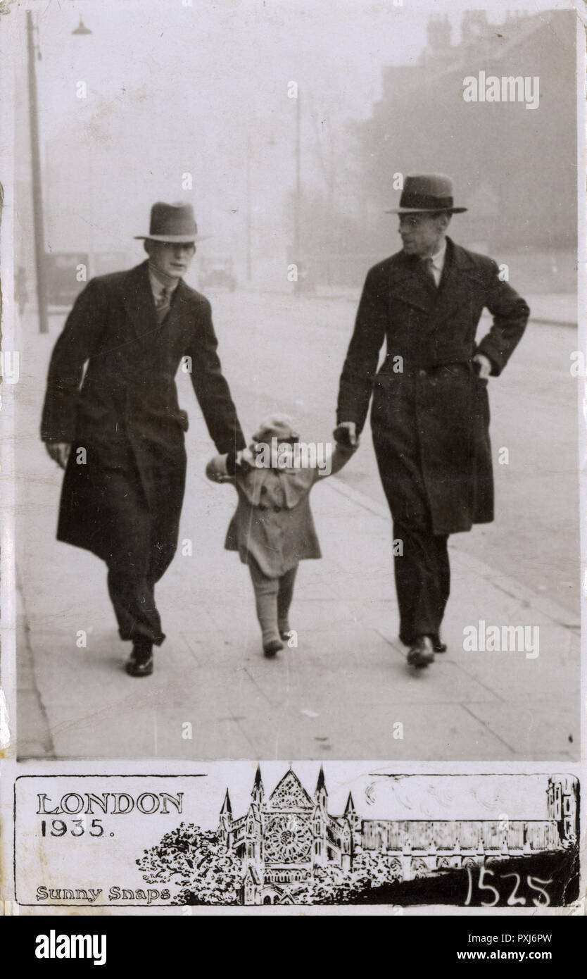 Young girl out for a stroll with her Father & Grandfather, London.     Date: 1935 - Stock Image
