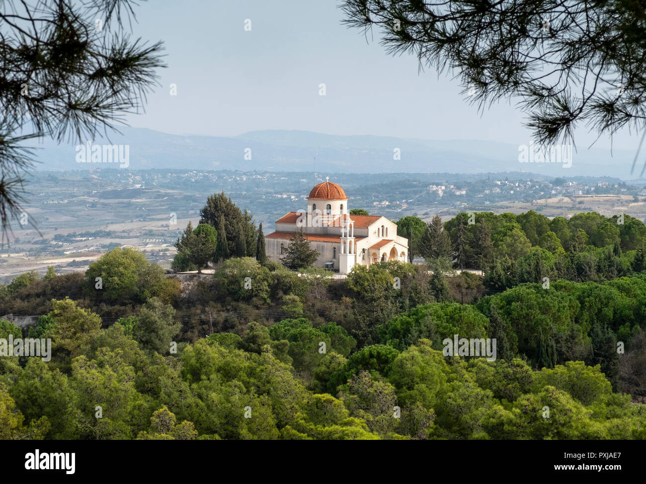 The church in the village of Pano Theletra sits on a elevated position surrounded by trees. - Stock Image