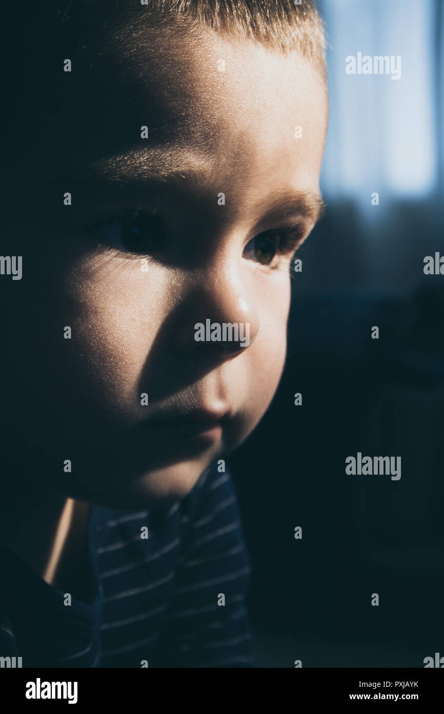 Portrait of a toddler watching TV in a dim light - Stock Image