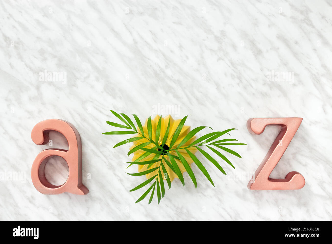 Metal letters A and Z, and green palm leaves in a yellow ceramic vase, on marble background. - Stock Image