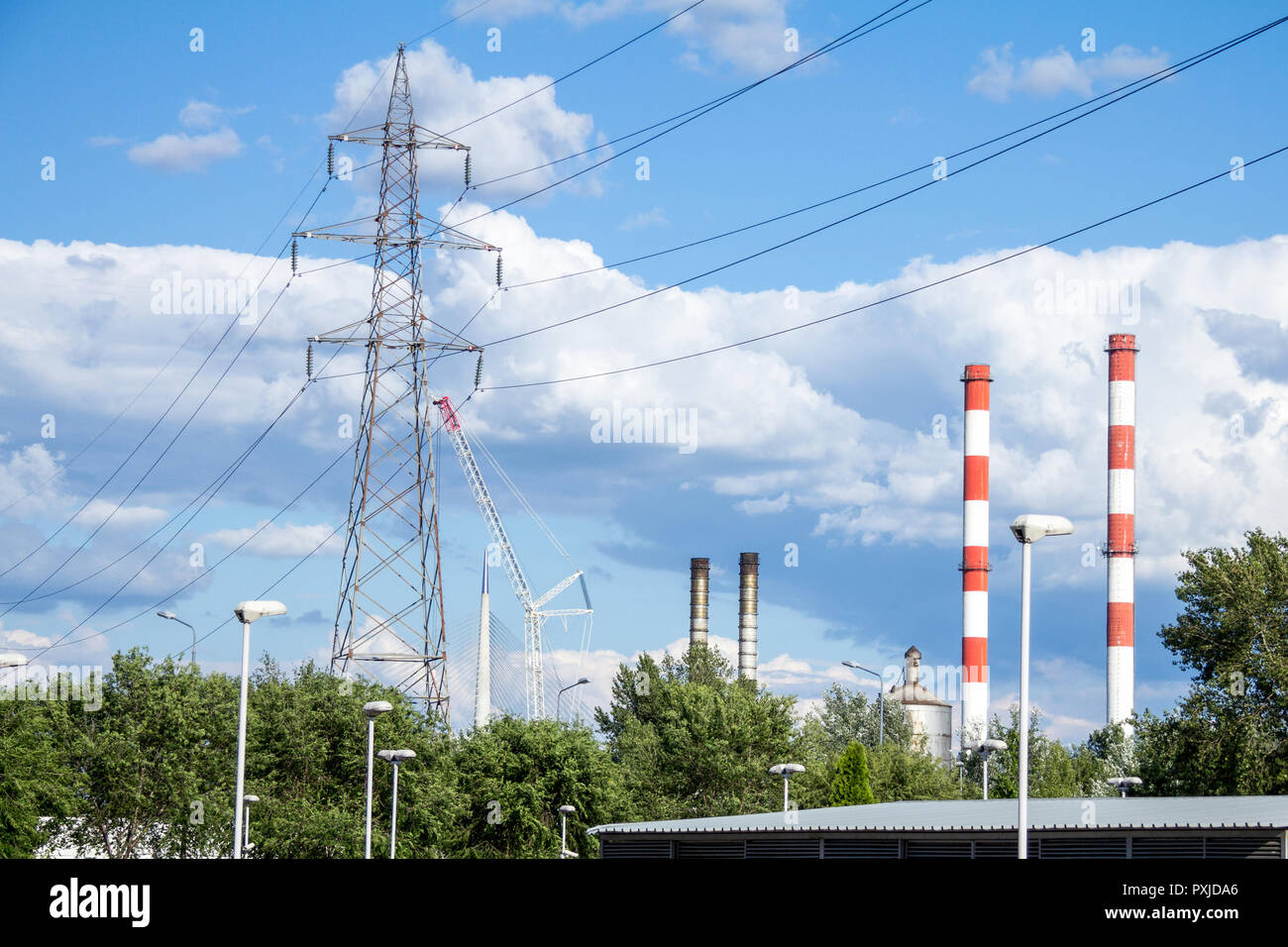 Industrial landscape of Eastern Europe, with transmission towers, pylons, power towers, factories and chimneys, taken during a sunny afternoon  Pictur - Stock Image