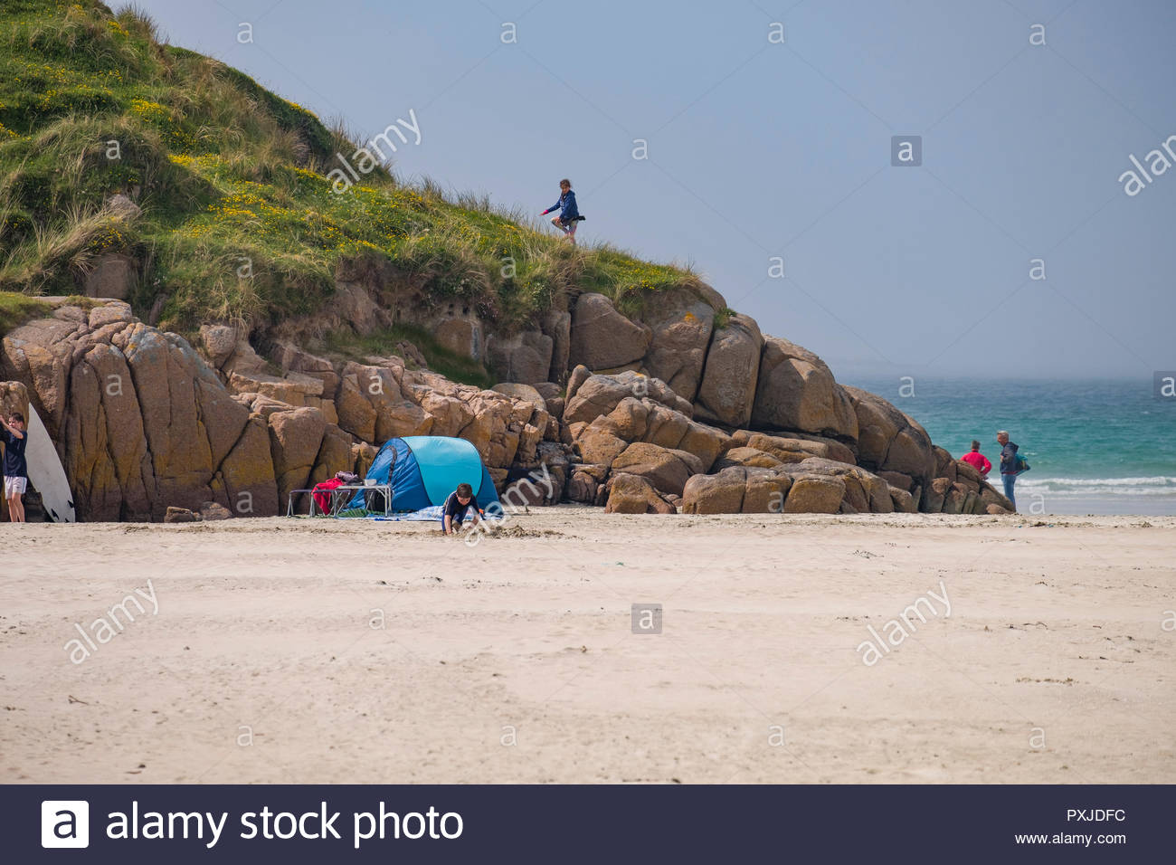 Girl climbing rocky coastline on Carrickfinn Beach a designated Blue Flag Beach on the Wild Atlantic Way, Braade, County Donegal, Ulster, Ireland - Stock Image