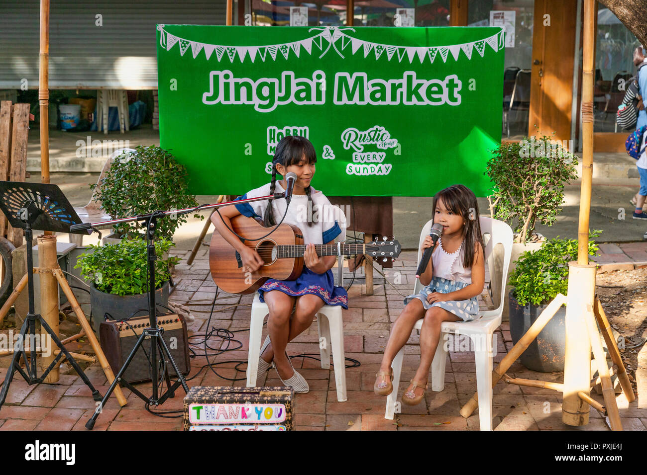 Talented young girls sing and play guitar at JingJai Farmer's Market, Chiang Mai, Thailand - Stock Image