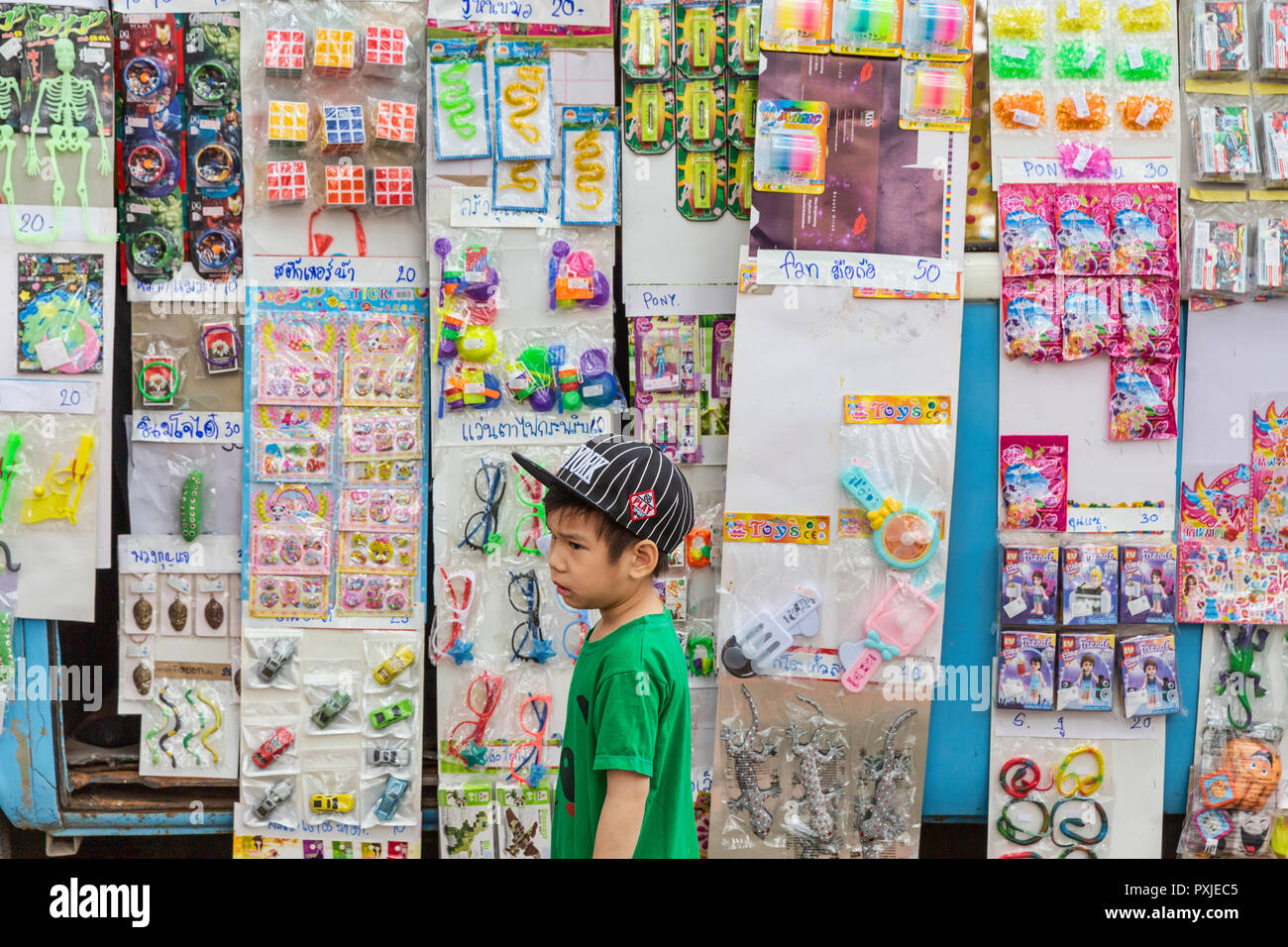Boy looks at toys for sale at converted VW van pop up toy shop at JingJai Farmer's Market, Chiang Mai, Thailand - Stock Image