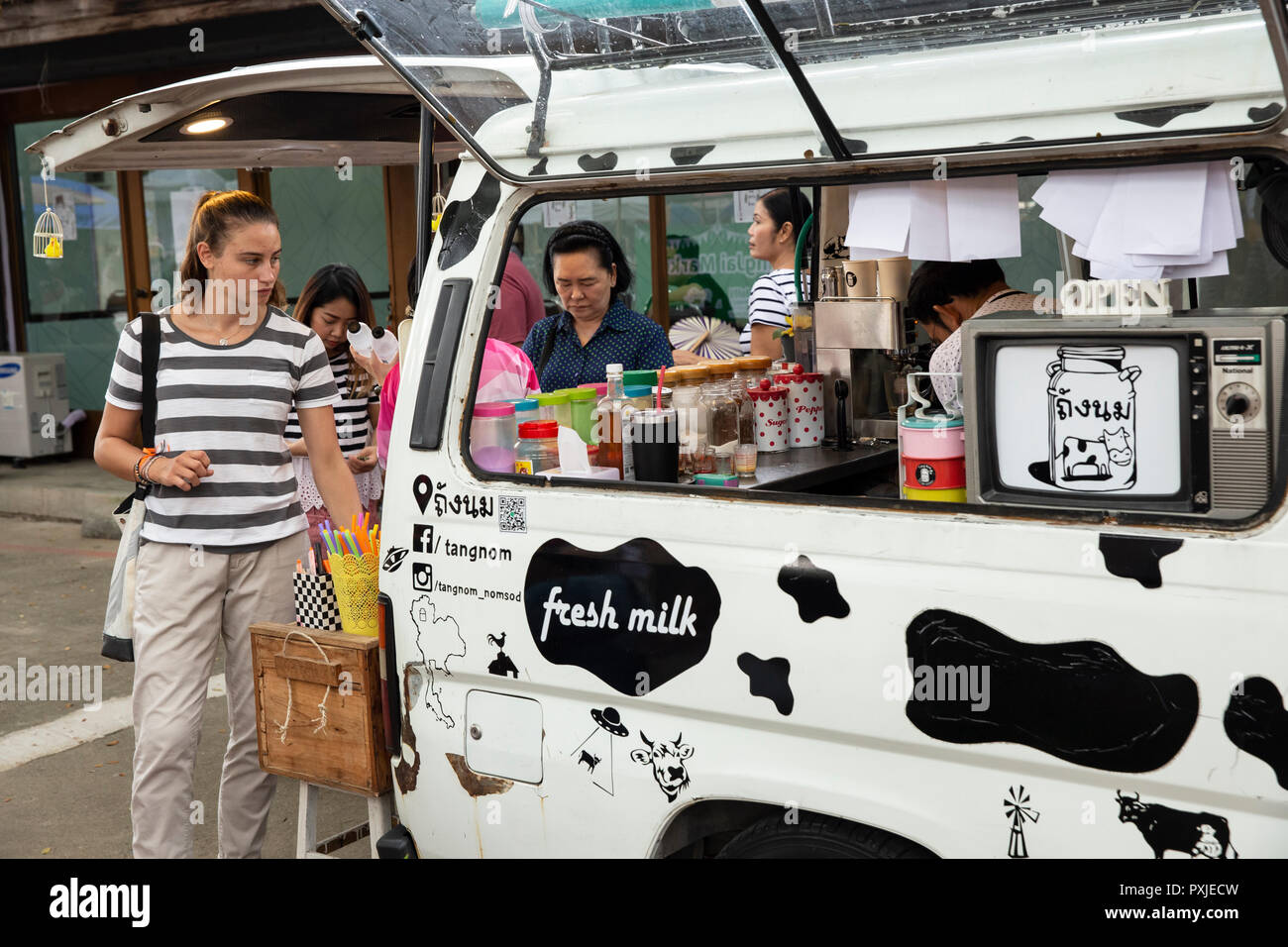 Tourist buys coffee at mobile coffee shop at JingJai Farmer's Market, Chiang Mai, Thailand - Stock Image