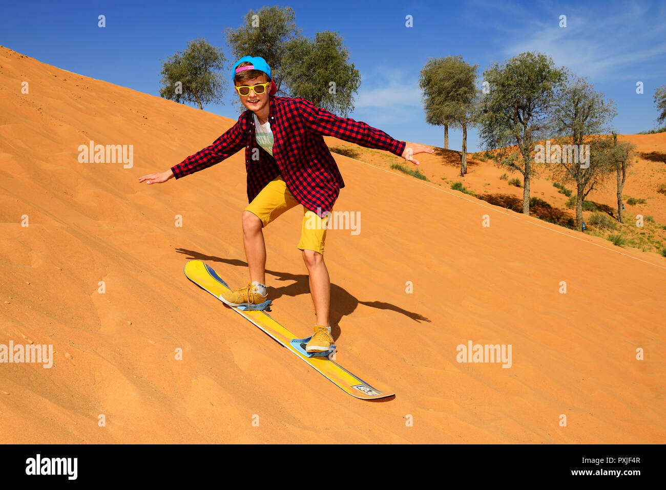 Tourist with Snowboard on the Dune, Ras al Khaimah, United Arab Emirates - Stock Image