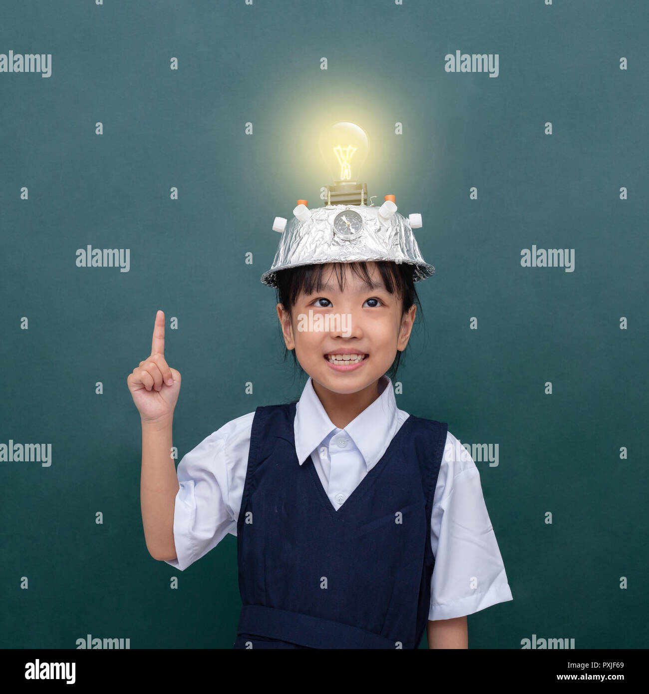 Asian chinese little girl wearing virtual reality helmet and pointing finger up to light bulb against green blackboard - Stock Image