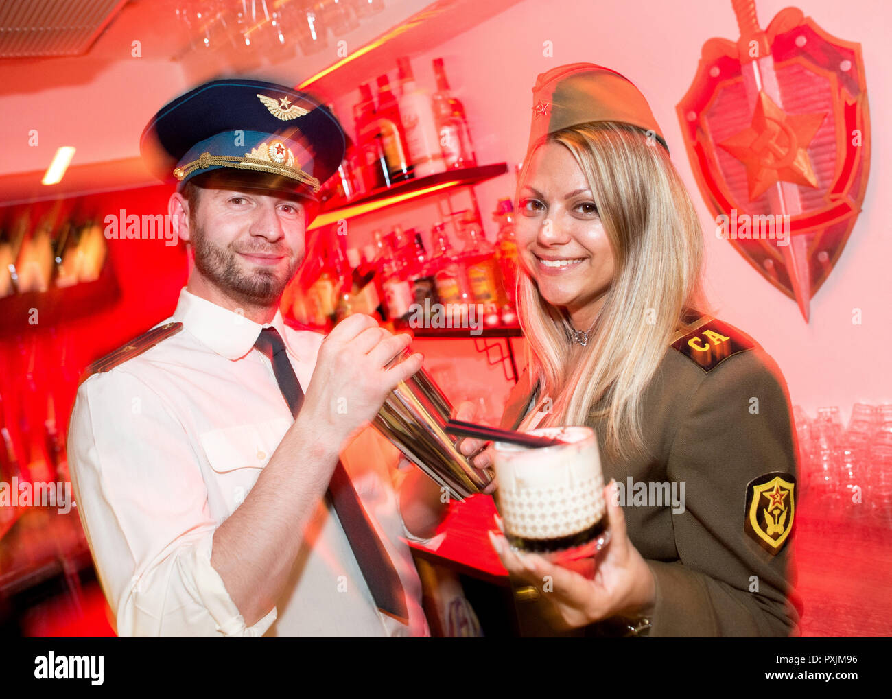 Hanover, Germany. 07th Apr, 2018. Bella and Anton stand behind the counter of the KGB bar in historical KGB uniforms. With many Soviet relics, the bar in the city centre of Hanover is reminiscent of the former USSR. Credit: Hauke-Christian Dittrich/dpa/Alamy Live News - Stock Image