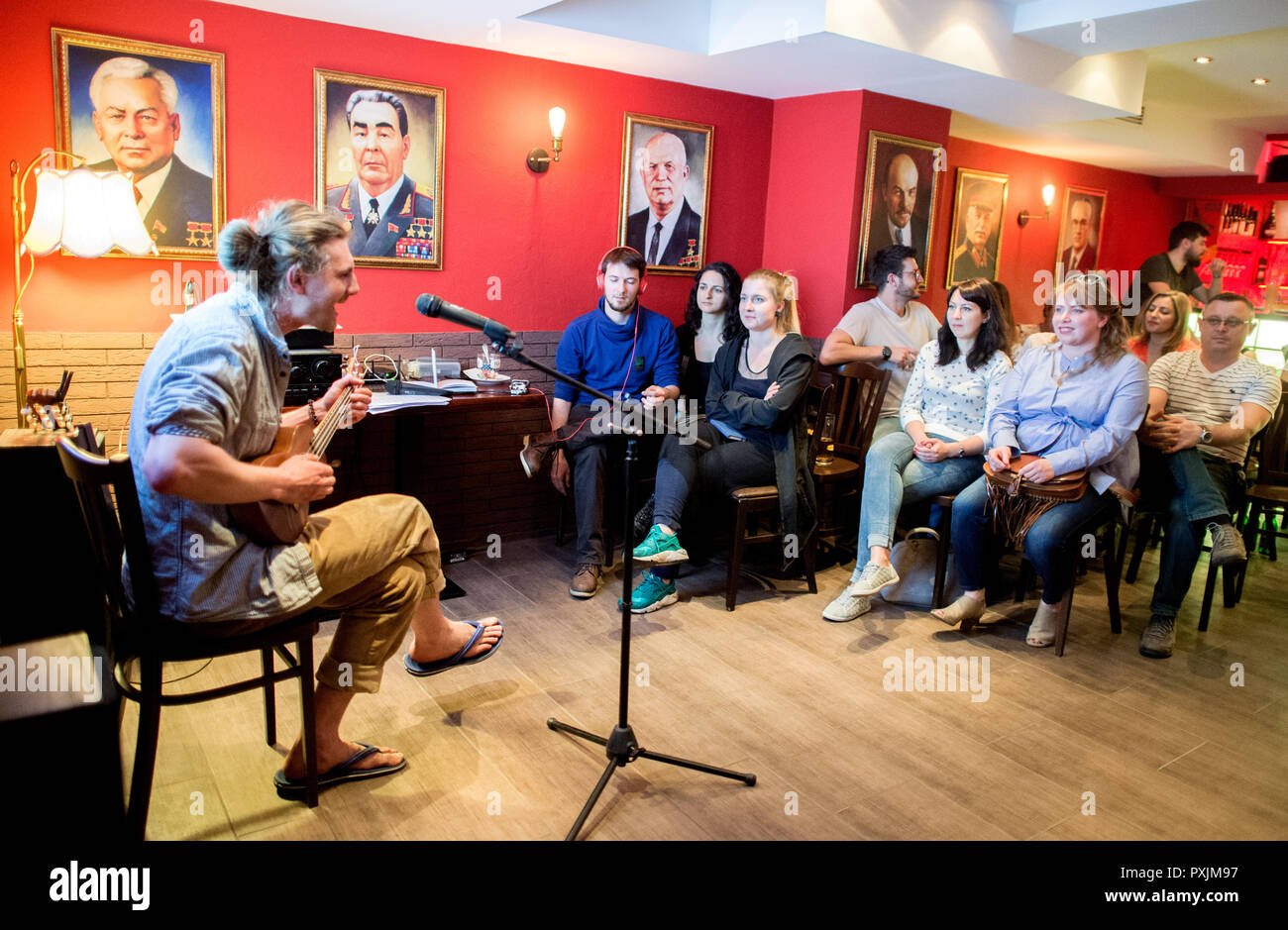 Hanover, Germany. 07th Apr, 2018. The musician Alexander Reyzin performs as part of a poetry slam in the KGB bar, while the portraits of former presidents hang in the background. With many Soviet relics, the bar in the city centre of Hanover is reminiscent of the former USSR. Credit: Hauke-Christian Dittrich/dpa/Alamy Live News - Stock Image
