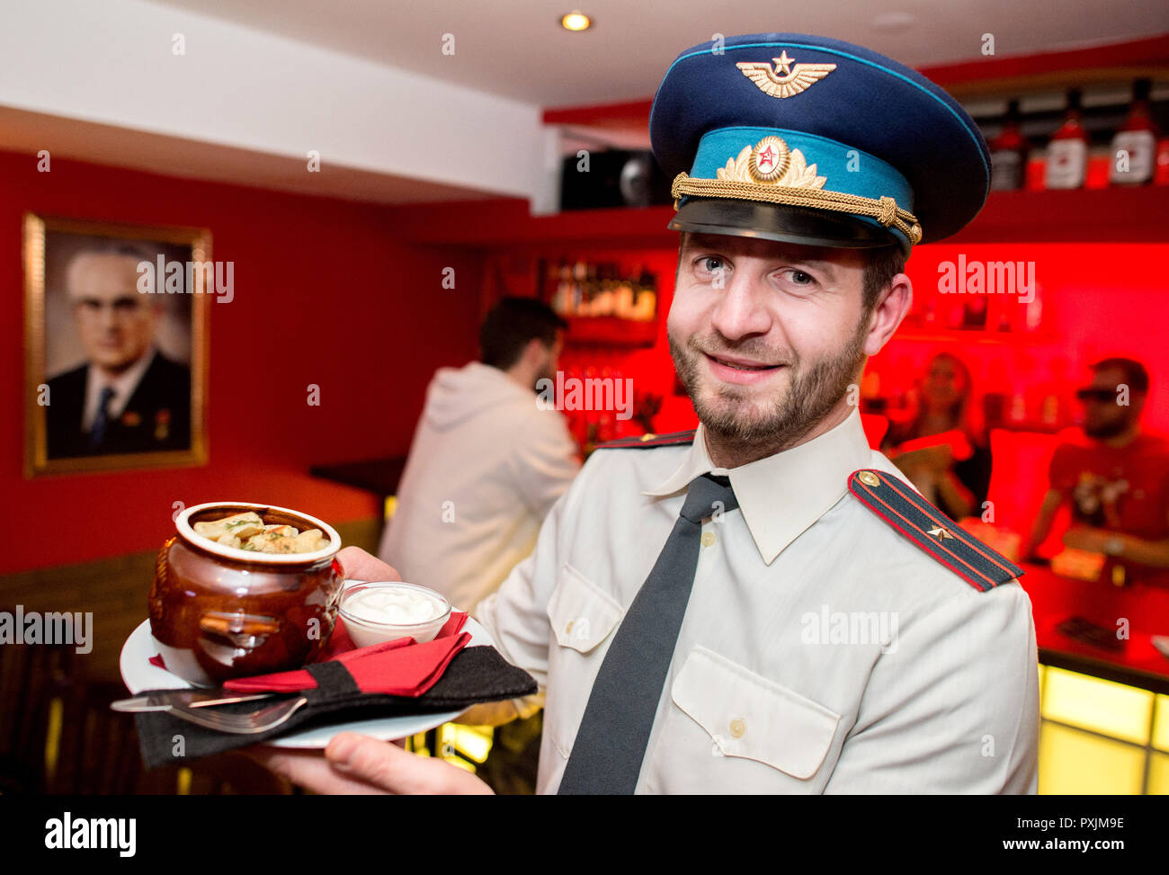Hanover, Germany. 07th Apr, 2018. Owner Anton Djacenko served in historical KGB uniform fresh Wareniki 'Ukraina', dumplings with potato filling, in the KGB bar. With many Soviet relics, the bar in the city centre of Hanover is reminiscent of the former USSR. Credit: Hauke-Christian Dittrich/dpa/Alamy Live News - Stock Image
