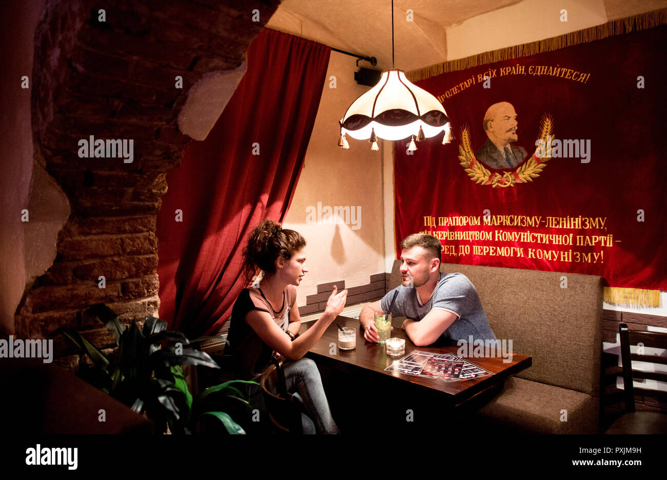 Hanover, Germany. 07th Apr, 2018. Guests chat in the KGB bar, while in the background hangs a flag showing the former Soviet head of government Vladimir Lenin. With many Soviet relics, the bar in the city centre of Hanover is reminiscent of the former USSR. Credit: Hauke-Christian Dittrich/dpa/Alamy Live News - Stock Image
