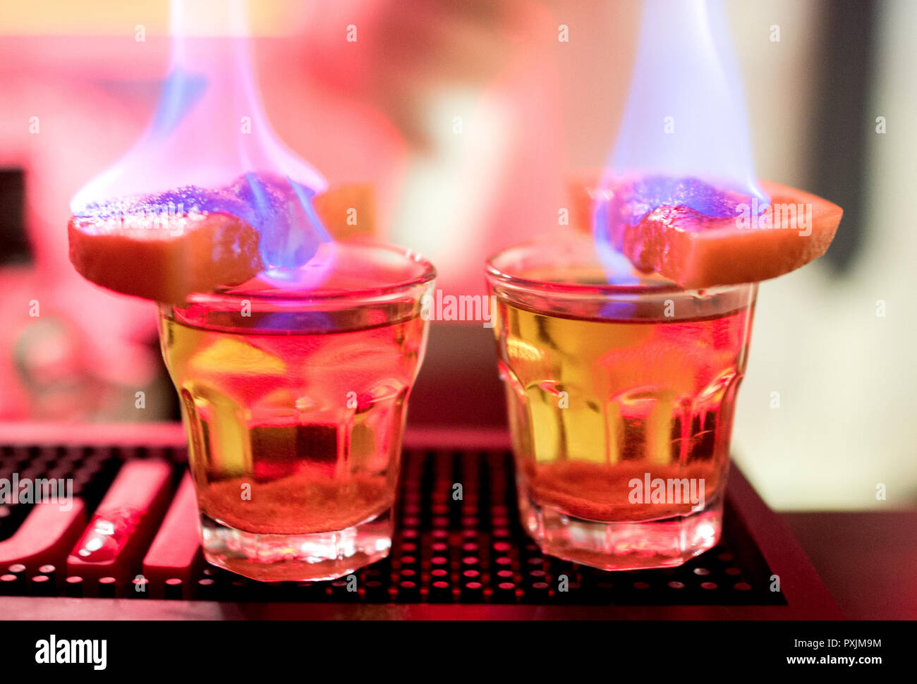 Hanover, Germany. 07th Apr, 2018. Two lighted schnapps with the name 'Kalashnikow' stand on a counter in the KGB bar. With many Soviet relics, the bar in the city centre of Hanover is reminiscent of the former USSR. Credit: Hauke-Christian Dittrich/dpa/Alamy Live News - Stock Image