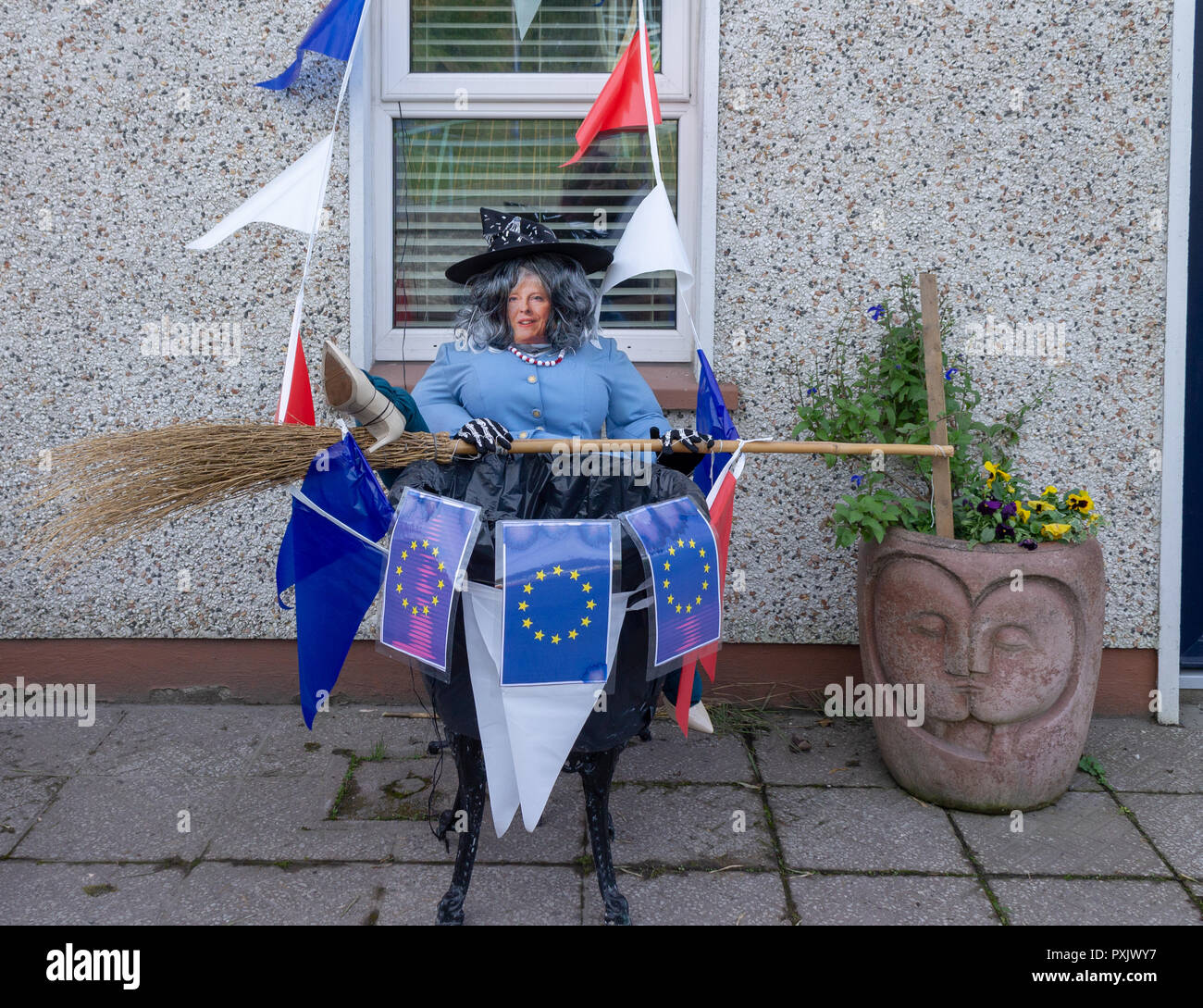 Theresa May scarecrow surrounded by european union flags depicted as the wicked witch of Brexit in a front garden as part of a scarecrow competition for Halloween - Stock Image