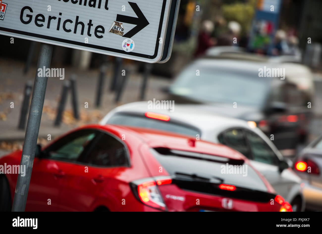 Mainz, Germany. 23rd Oct, 2018. Cars drive past a sign to the courthouse. Next Wednesday (24 October), the Administrative Court in Mainz will deal with a lawsuit filed by the German Environmental Aid (DUH) against the city of Mainz because of its plan for air pollution control and excessively high pollutant levels. NO2 can irritate the airways and eyes, disrupt lung function or lead to cardiovascular disease. Credit: Andreas Arnold/dpa/Alamy Live News - Stock Image