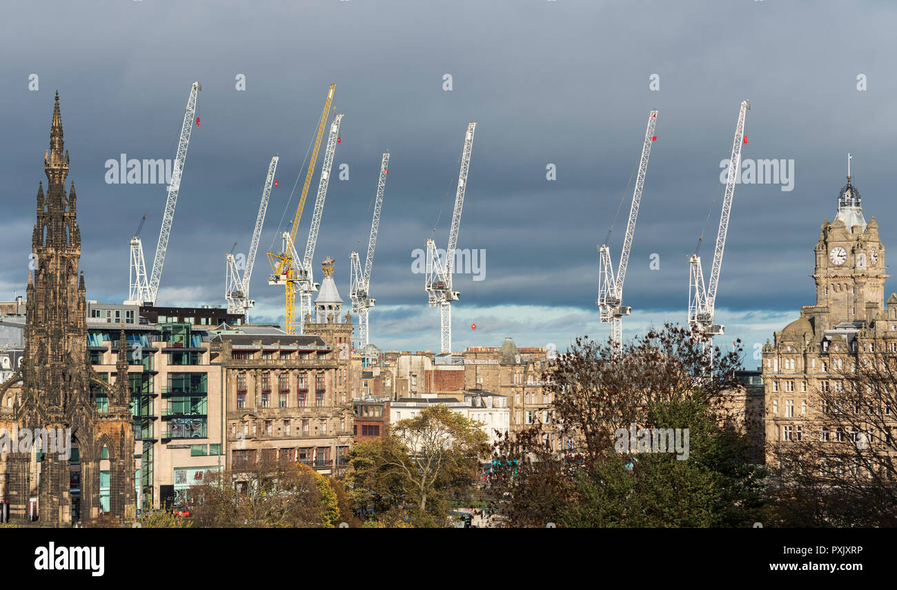 Edinburgh, Scotland, UK. 23 October, 2018. High winds throughout the day with gusts up to 50km/h forced construction site tower cranes to cease work at the large St James Centre redevelopment construction site. Cranes are free to turn with the wind and are seen lined up in a row against the skyline of the city. Credit: Iain Masterton/Alamy Live News - Stock Image