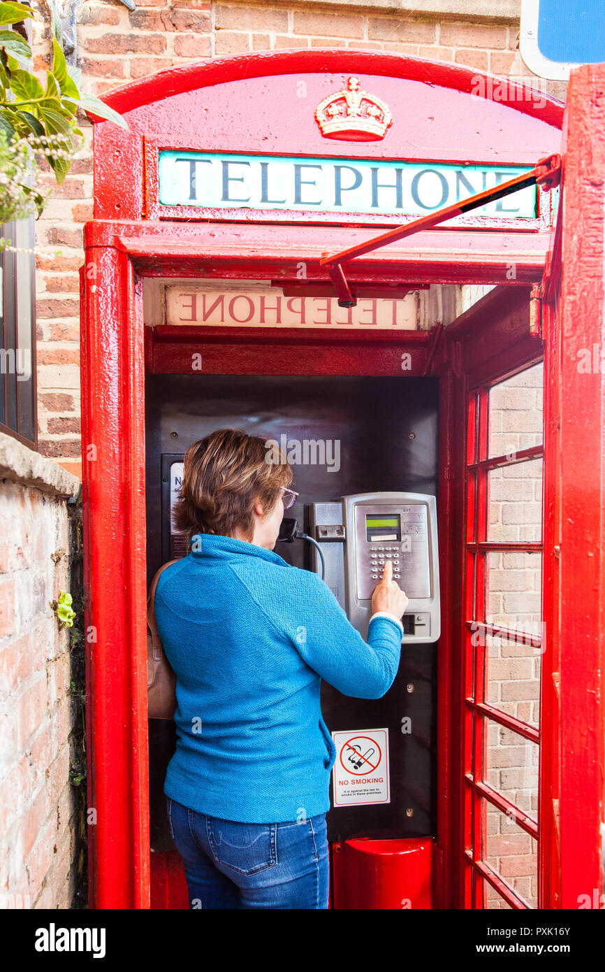Woman chatting talking using a telephone in an traditional red English telephone box kiosk design  no 6  / K6 designed in 1935 by Sir Gilbert Scott - Stock Image