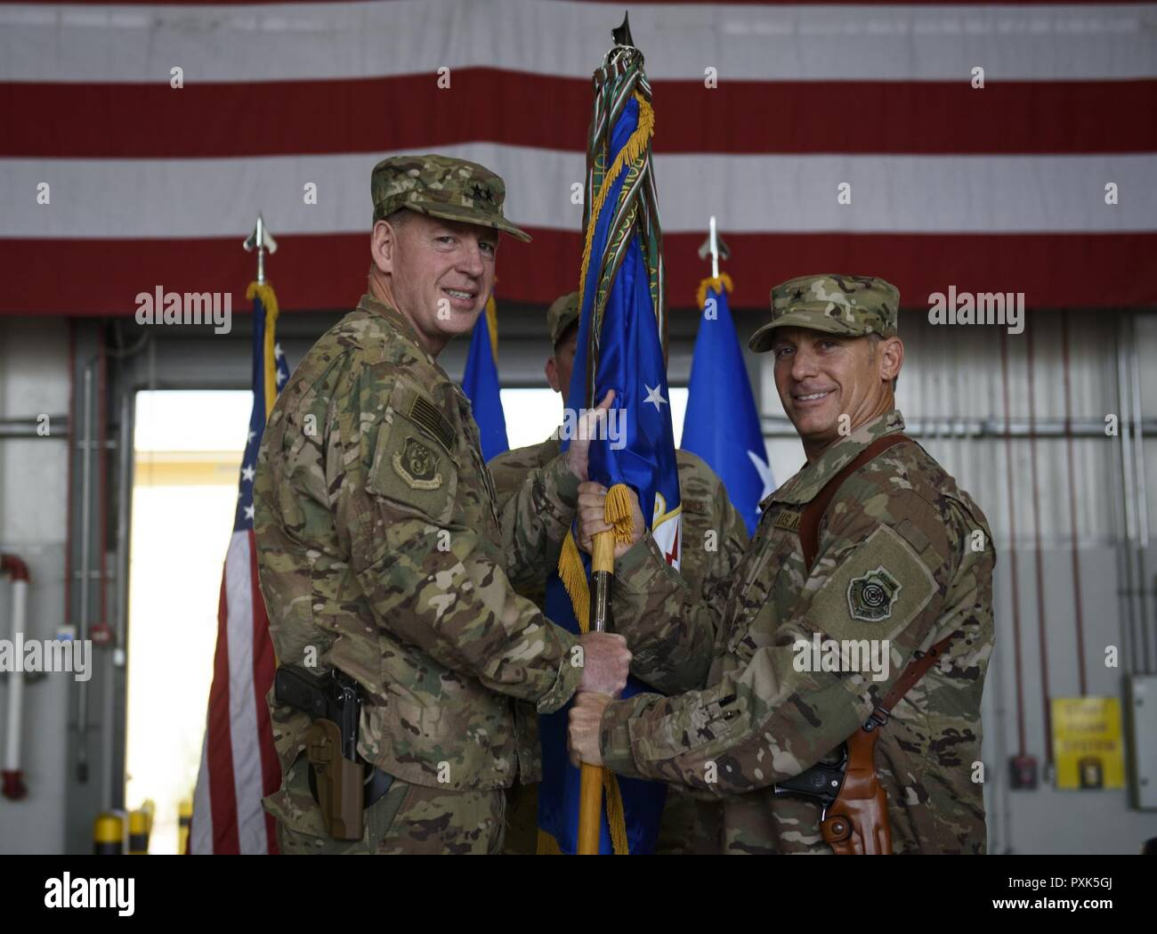 Brig. Gen. Craig Baker, the incoming 455th Air Expeditionary Wing commander, receives the 455th AEW guidon from Maj. Gen. James Hecker, the 9th Air and Space Expeditionary Task Force-Afghanistan commander, which officially grants him command of the 455th AEW during a change of command ceremony at Bagram Airfield, Afghanistan, June 3, 2017. Baker is a command pilot with more than 2,600 flying hours and has commanded at the Squadron and Wing level. Stock Photo