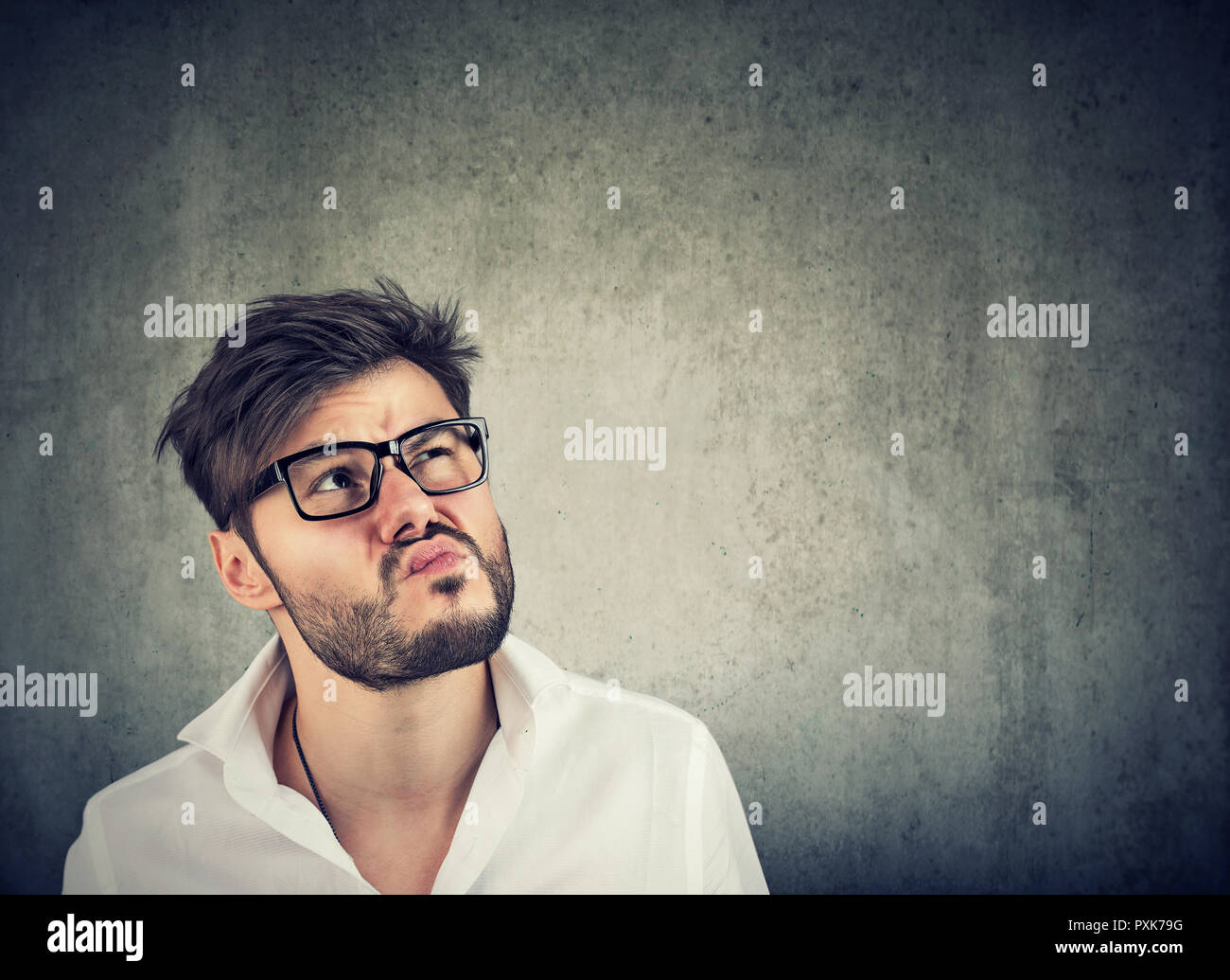 Adult bearded man in glasses and white shirt looking up in thoughts being uncertain on gray background - Stock Image