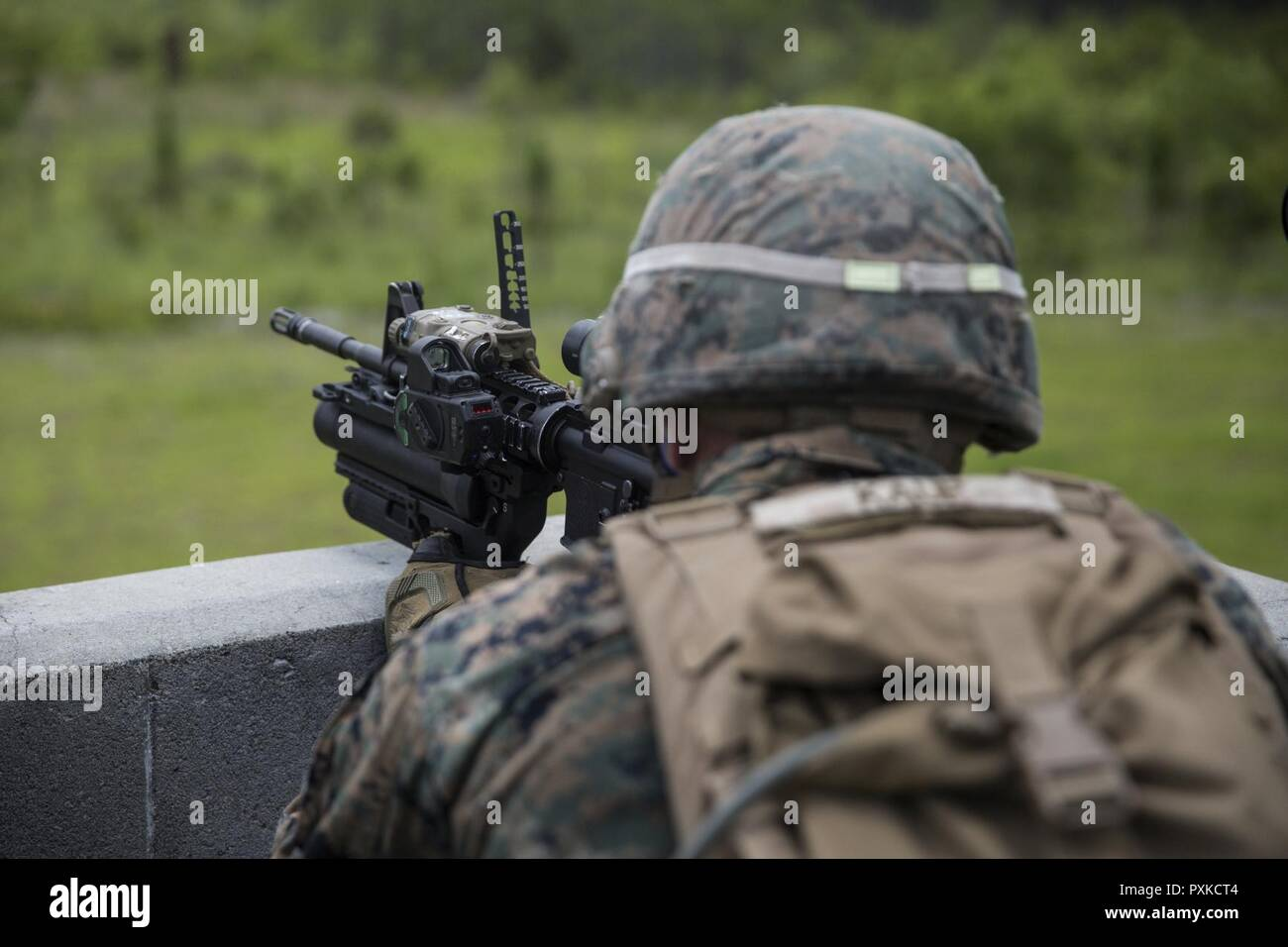 A Marine Observes Target Through Sight On An M320 Grenade Launcher Mounted
