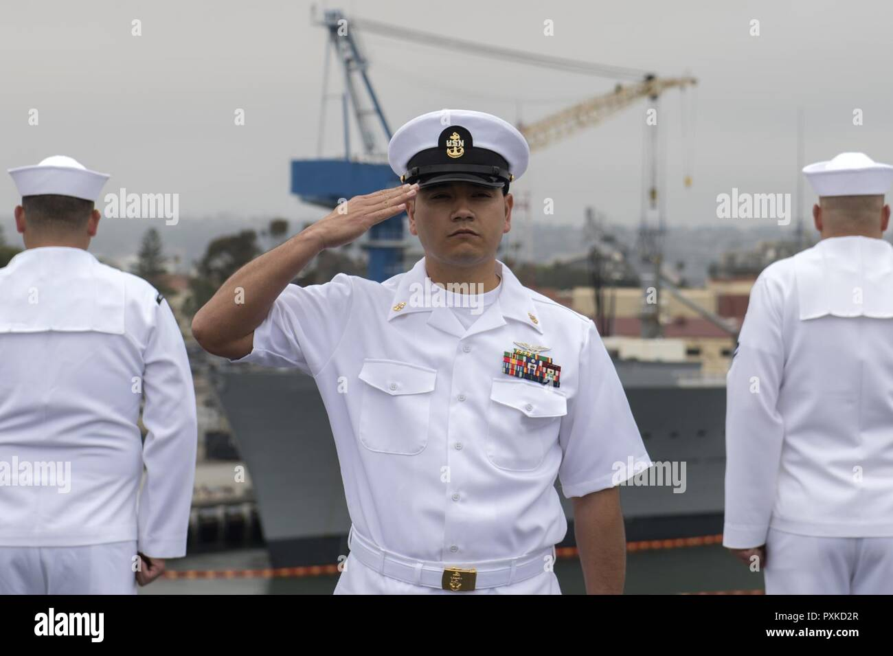 SAN DIEGO (June 5, 2017)  Chief Aviation Machinist's Mate Rodrigo Zurita renders honors to the USS Midway (CV 41) Aircraft Carrier Museum as the aircraft carrier USS Nimitz (CVN 68) passes on the 75th anniversary of the Battle of Midway, June 5, 2017, in San Diego. Nimitz is joining Carrier Air Wing 11, Destroyer Squadron 9 and the rest of Carrier Strike Group 11 to depart on a regularly scheduled deployment. - Stock Image