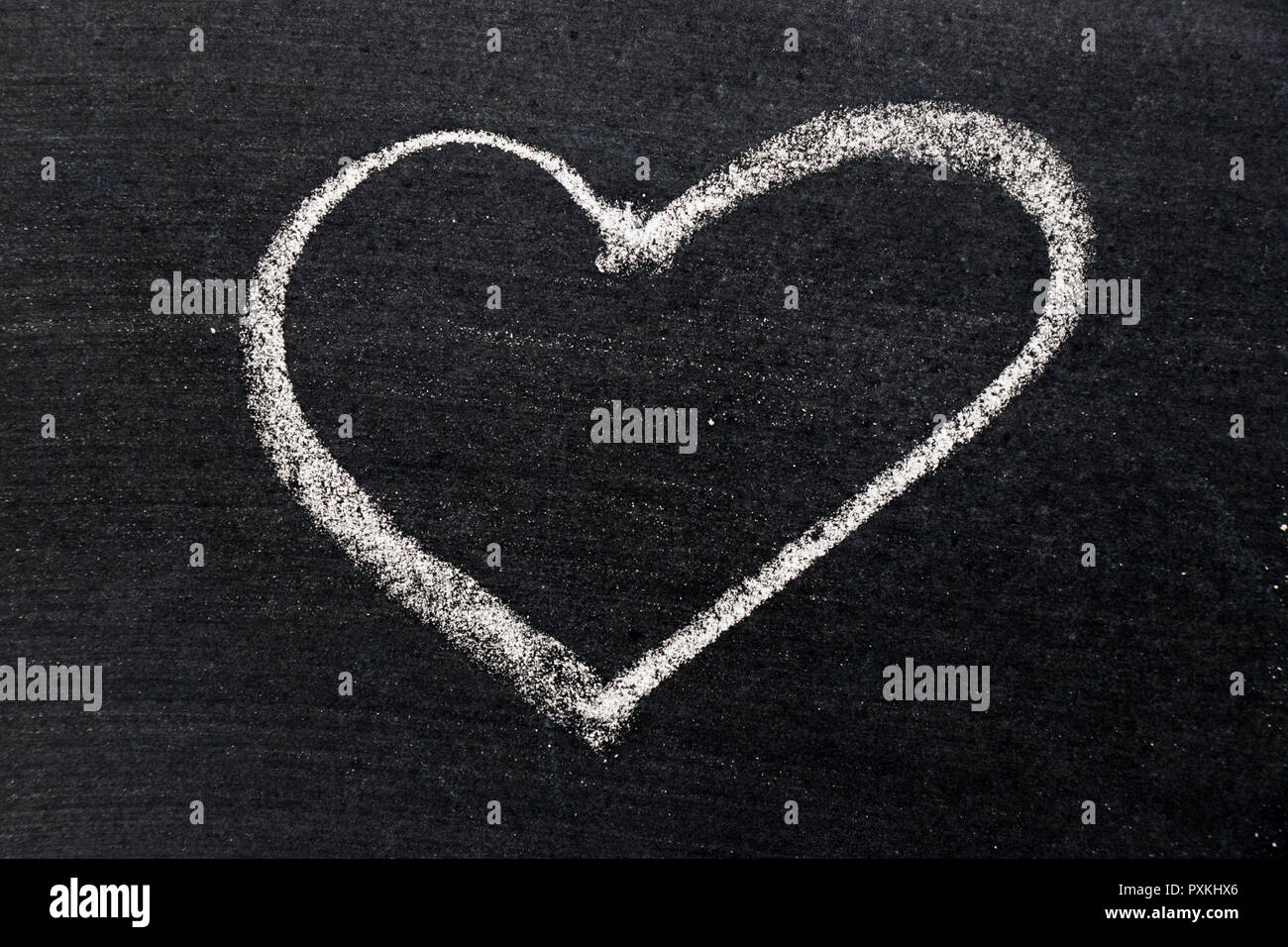 White chalk drawing in heart shape on black board background use for decoration in valentine, love, couple or engagement concept - Stock Image