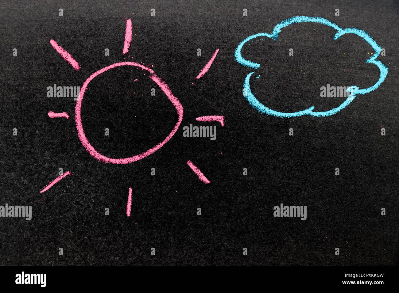 Chalk drawing as pink sun and blue cloud on black board background - Stock Image